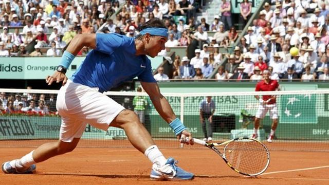 Rafael Nadal of Spain returns the ball to Roger Federer of Switzerland during their men's final at the French Open tennis tournament at the Roland Garros stadium in Paris June 5, 2011