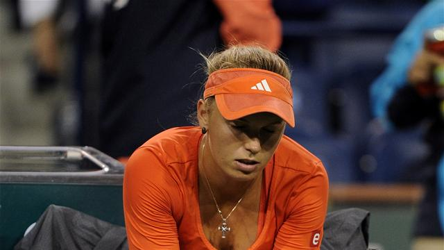 Wozniacki withdraws, Serena through