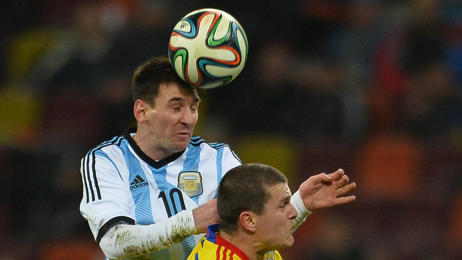 Lionel Messi (L) of Argentina vies for the ball against Cristian Bourceanu