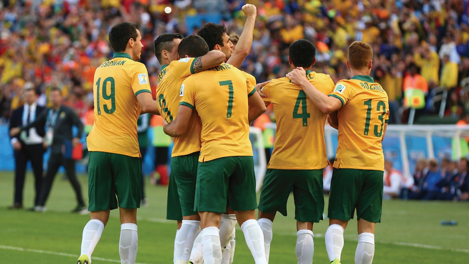 Mile Jedinak of Australia celebrates scoring his team's second goal with his teammates during the 2014 FIFA World Cup Brazil
