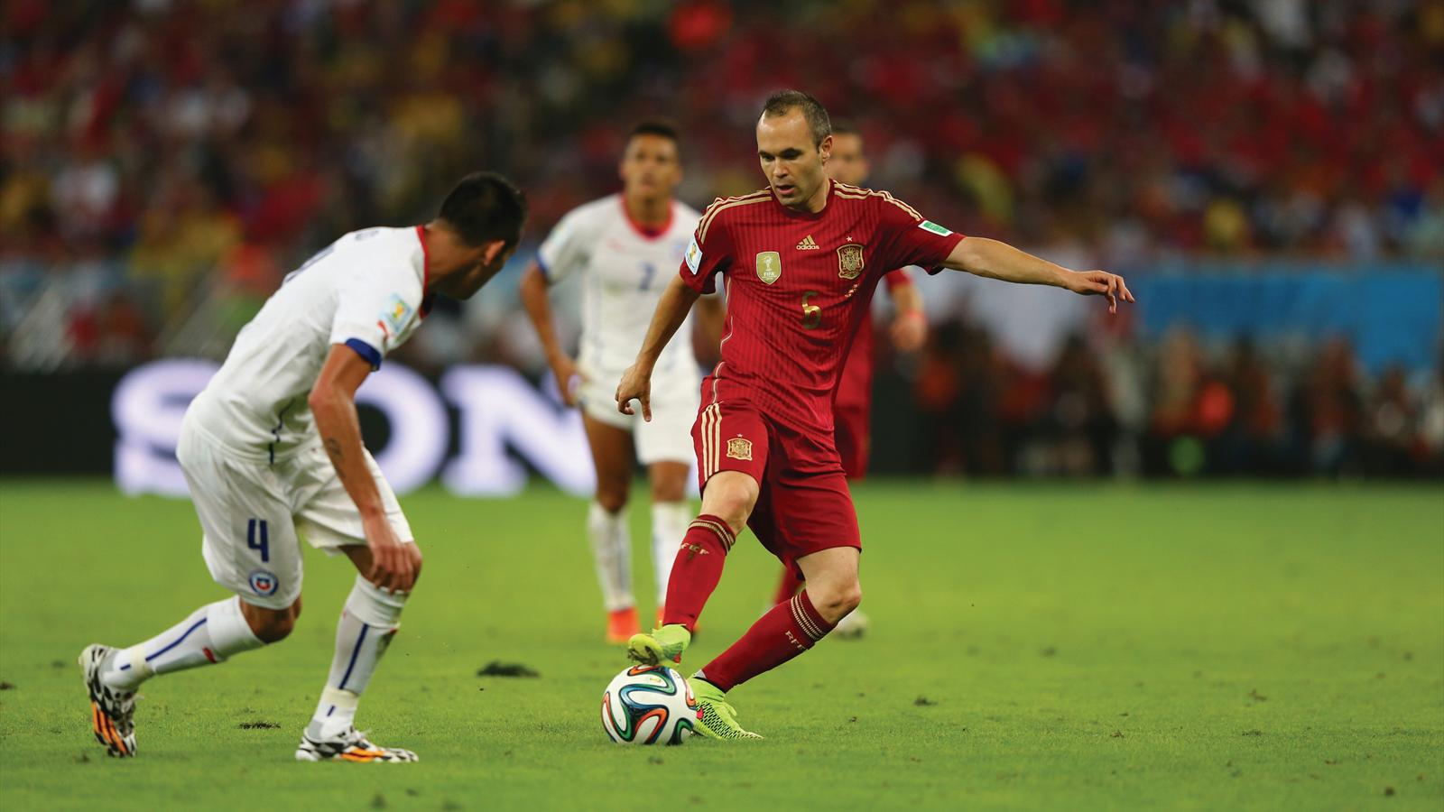 Andres Iniesta of Spain and Mauricio Isla of Chile compete for the ball during the 2014 FIFA World Cup Brazil
