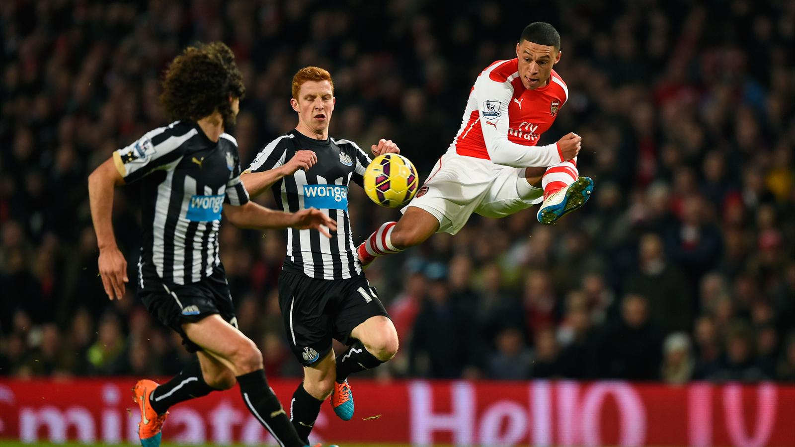 Alex Oxlade-Chamberlain of Arsenal controls the ball under pressure from Newcastle players.