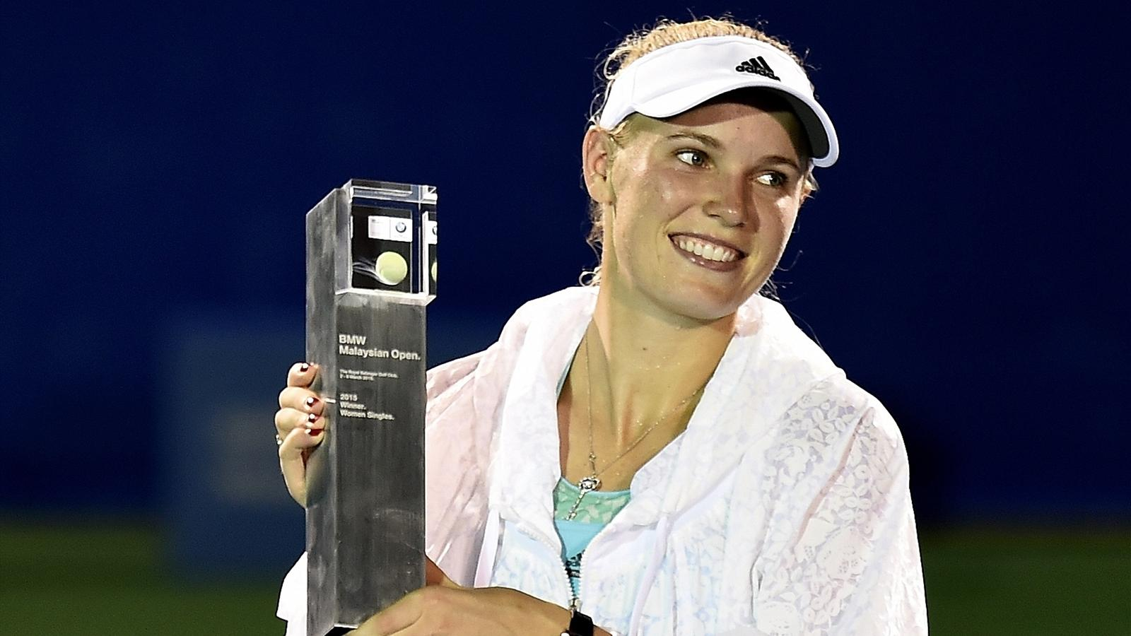 Caroline Wozniacki of Denmark poses with the trophy after defeating Romania's Alexandra Dulgheru during their women's singles final match of the 2015 BMW Malaysia Open tennis tournament in Kuala Lumpur on March 8, 2015.
