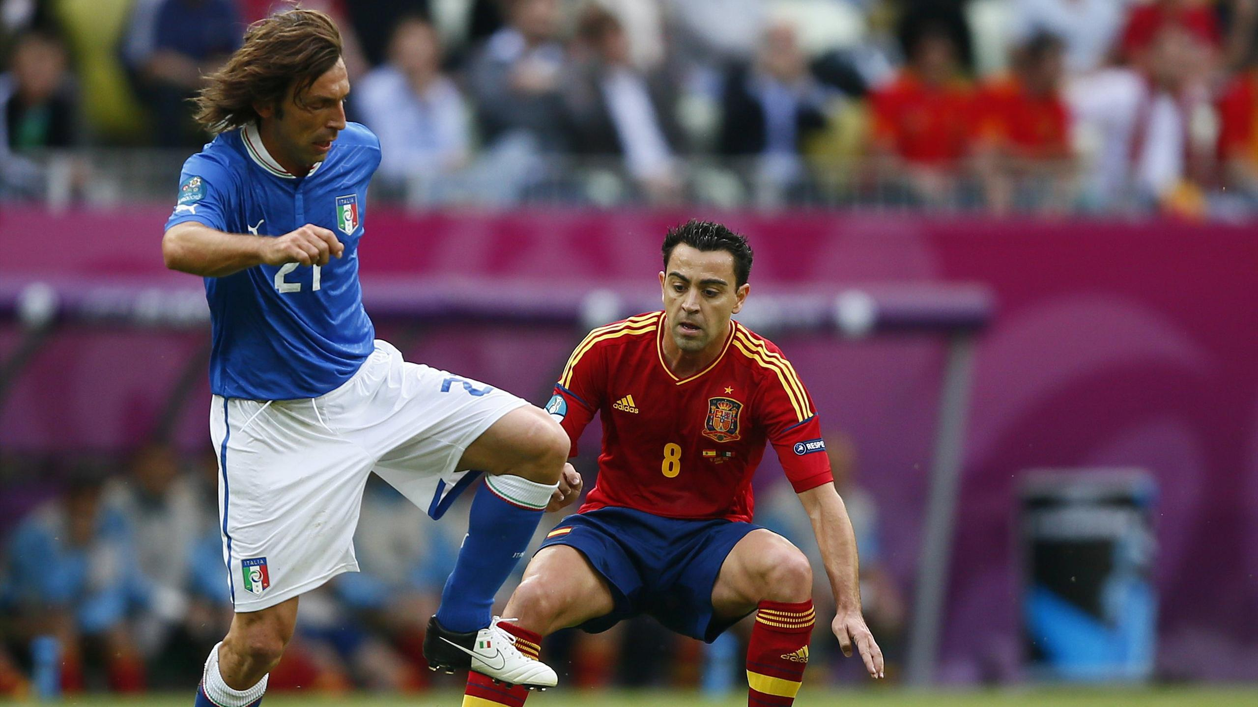 Italy's Andrea Pirlo (L) and Spain's Xavi Hernandez (R) challenge for the ball