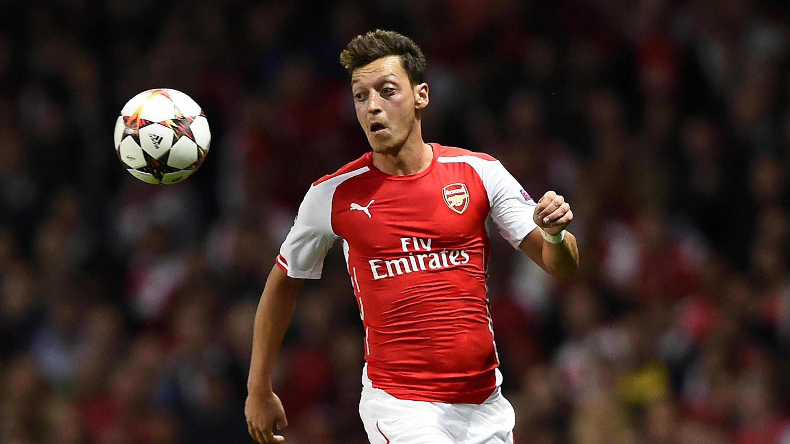 Arsenal's Mesut Ozil runs for the ball during their Champions League playoff soccer match against Besiktas at the Emirates stadium in London August 27, 2014