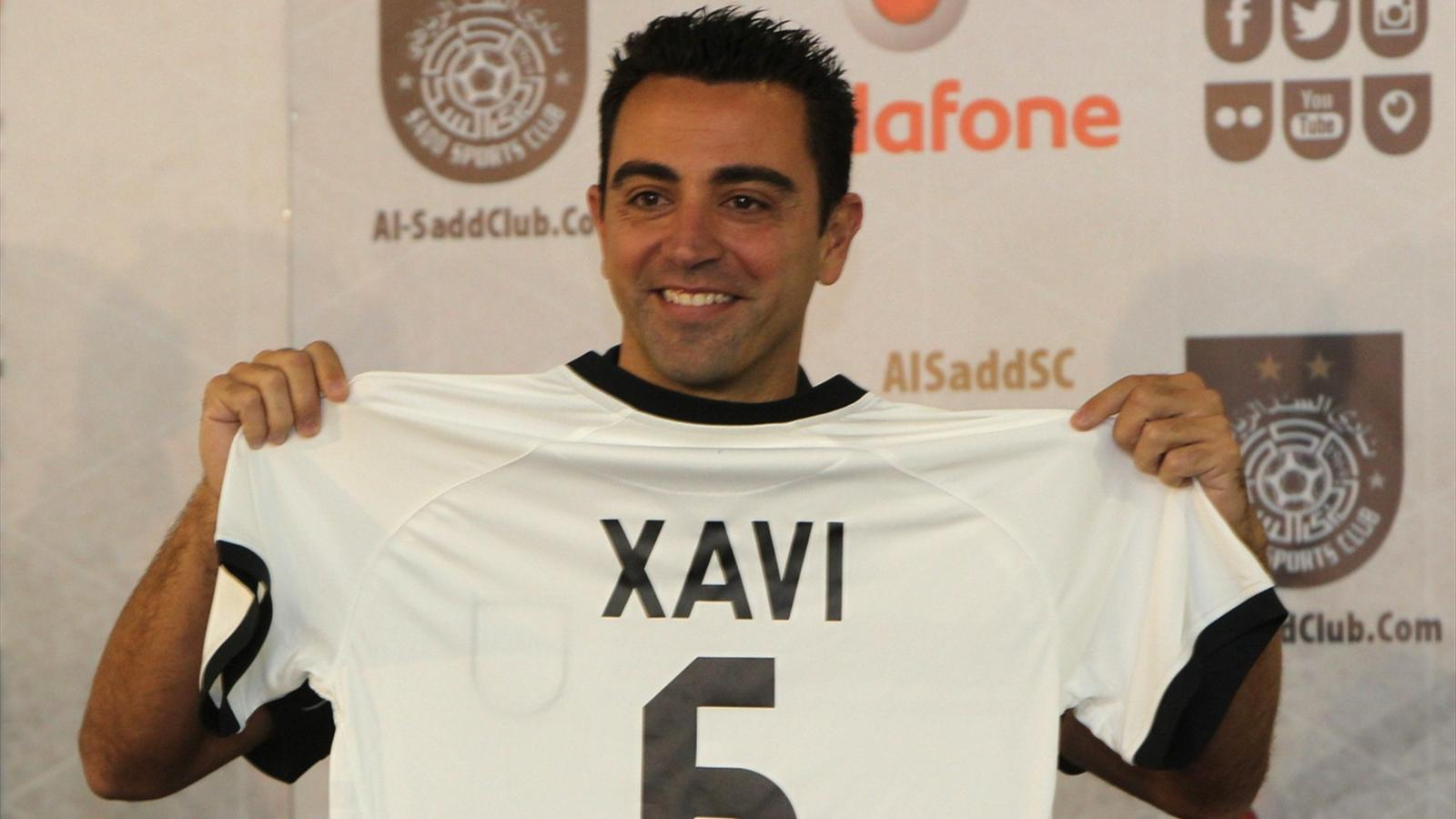 Barcelona legend Xavi Hernandez gestures in his new Al-Sadd club shirt after signing a two-year contract with the Qatari football team in Doha on June 11, 2015