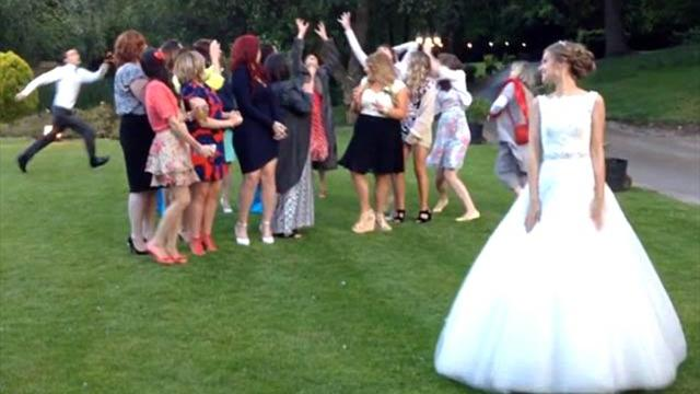 Video: Groom stuns wedding guests by volleying bouquet from bride