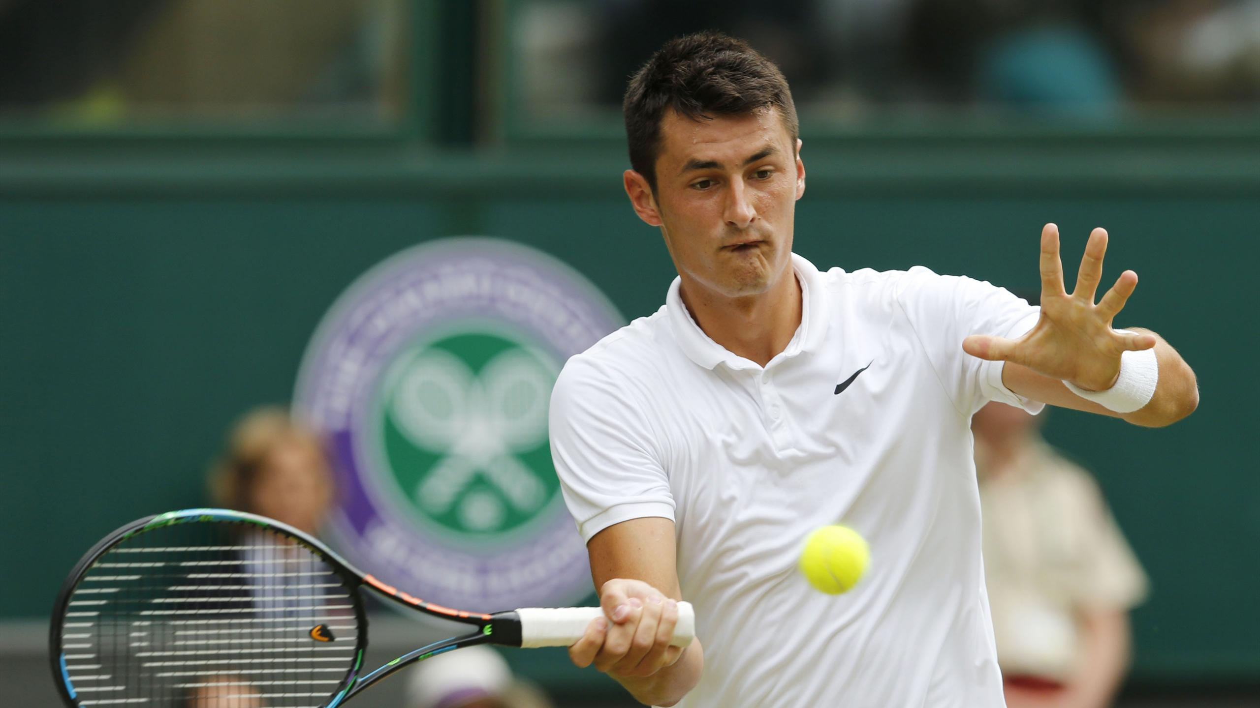 Bernard Tomic of Australia hits a shot during his match against Novak Djokovic