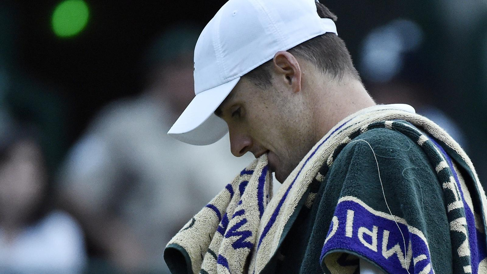 John Isner of the U.S.A. bites his towel during his match against Marin Cilic