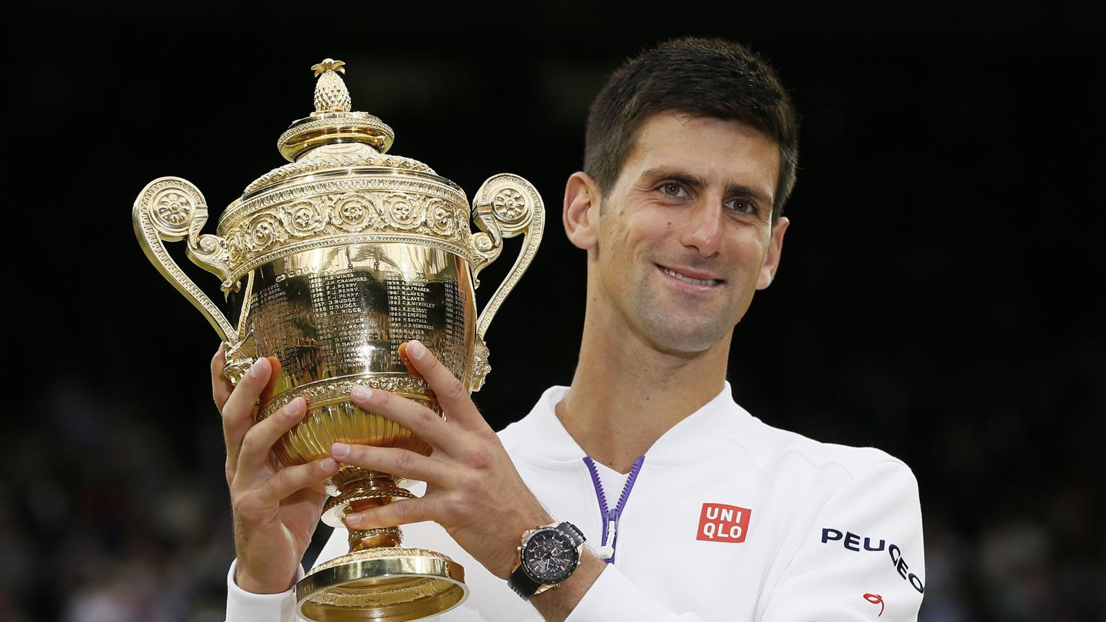 Novak Djokovic of Serbia shows off the trophy after winning his Men's Singles Final match against Roger Federer of Switzerland at the Wimbledon Tennis Championships in London, July 12, 2015. REUTERS/Stefan Wermuth