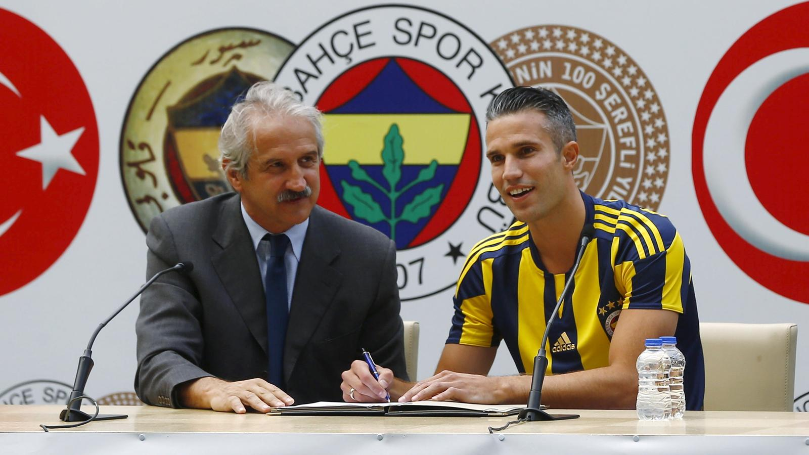 Netherlands striker Robin van Persie (R) poses for the media during his contract-signing ceremony