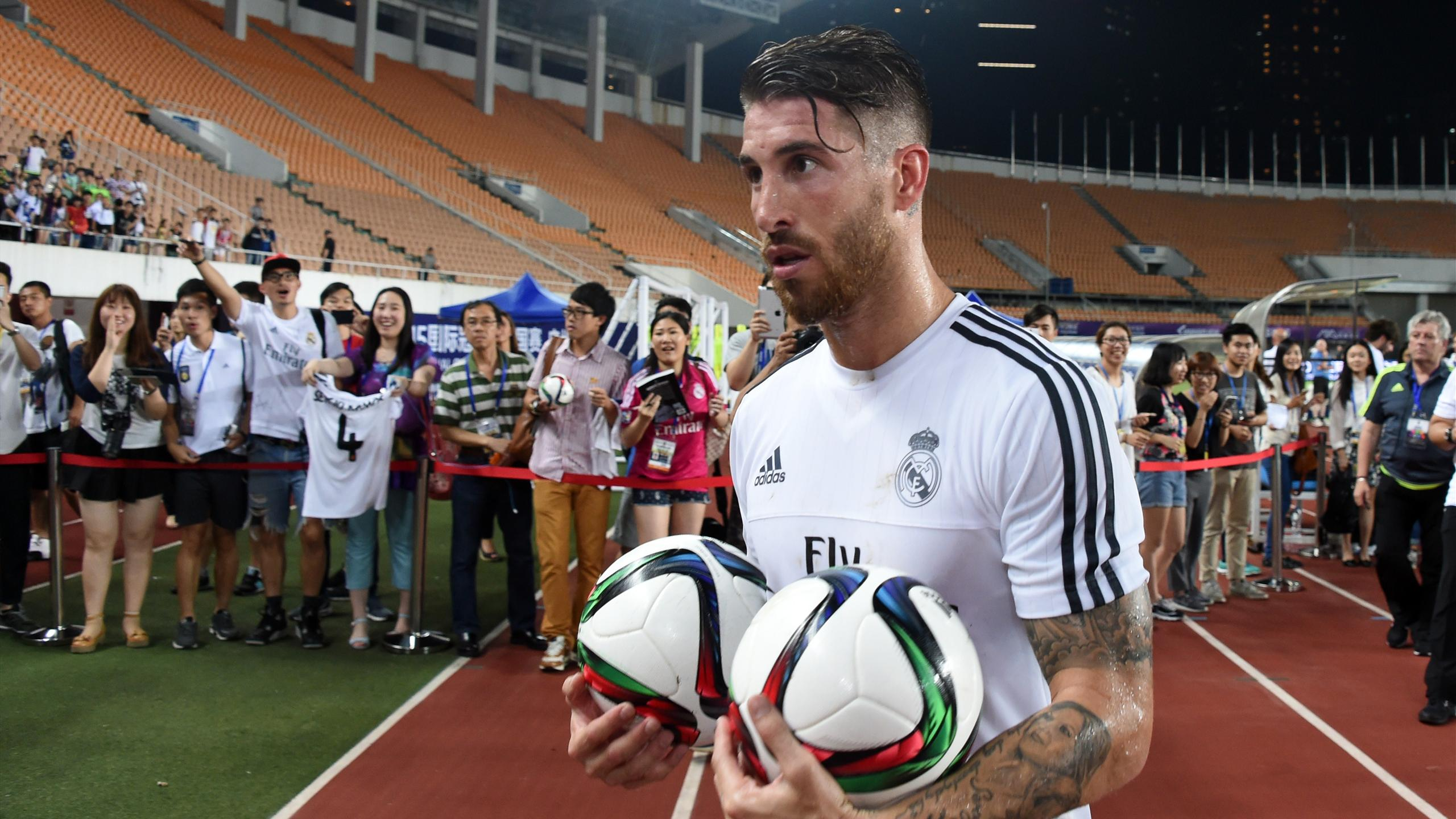 Real Madrid's defender Sergio Ramos holds two ball after a training session on the eve of the International Champions Cup football match between Inter Milan and Real Madrid in Guagnzhou on July 26, 2015.