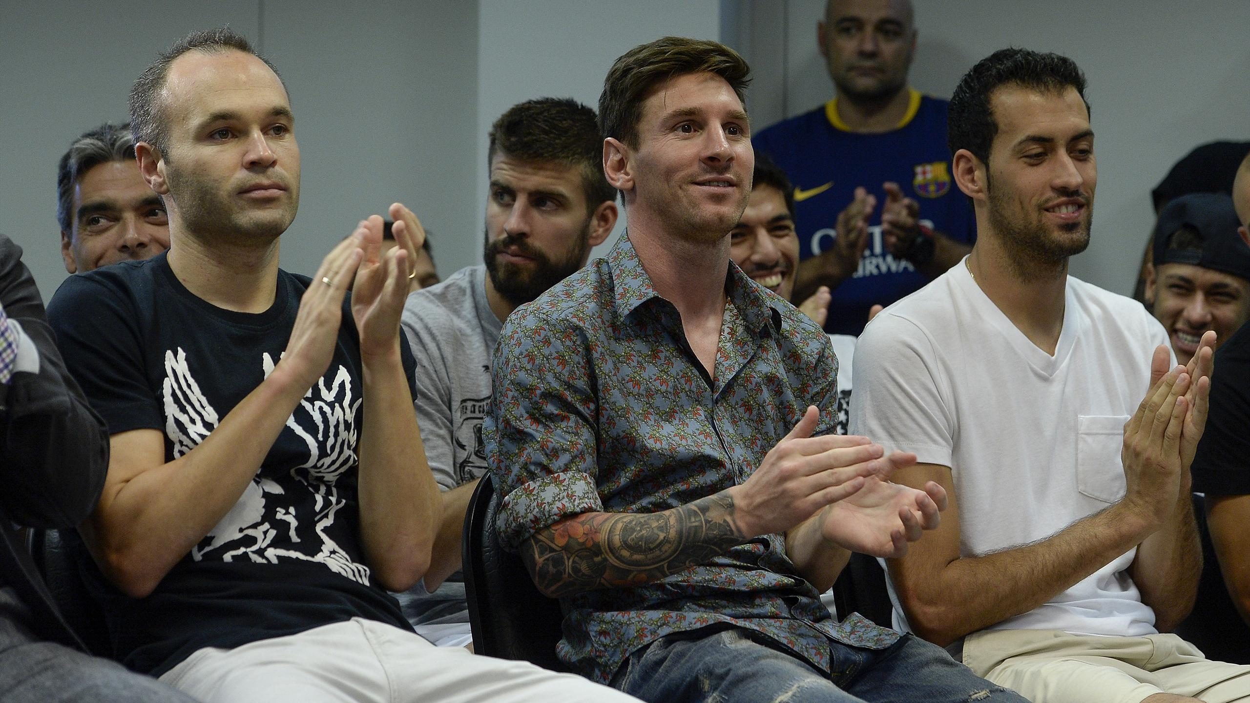 Barcelona's Argentinian forward Lionel Messi (C), Barcelona's midfielder Andres Iniesta and Barcelona's midfielder Sergio Busquets (R) clap during a farewell press conference for Barcelona's former forward Pedro
