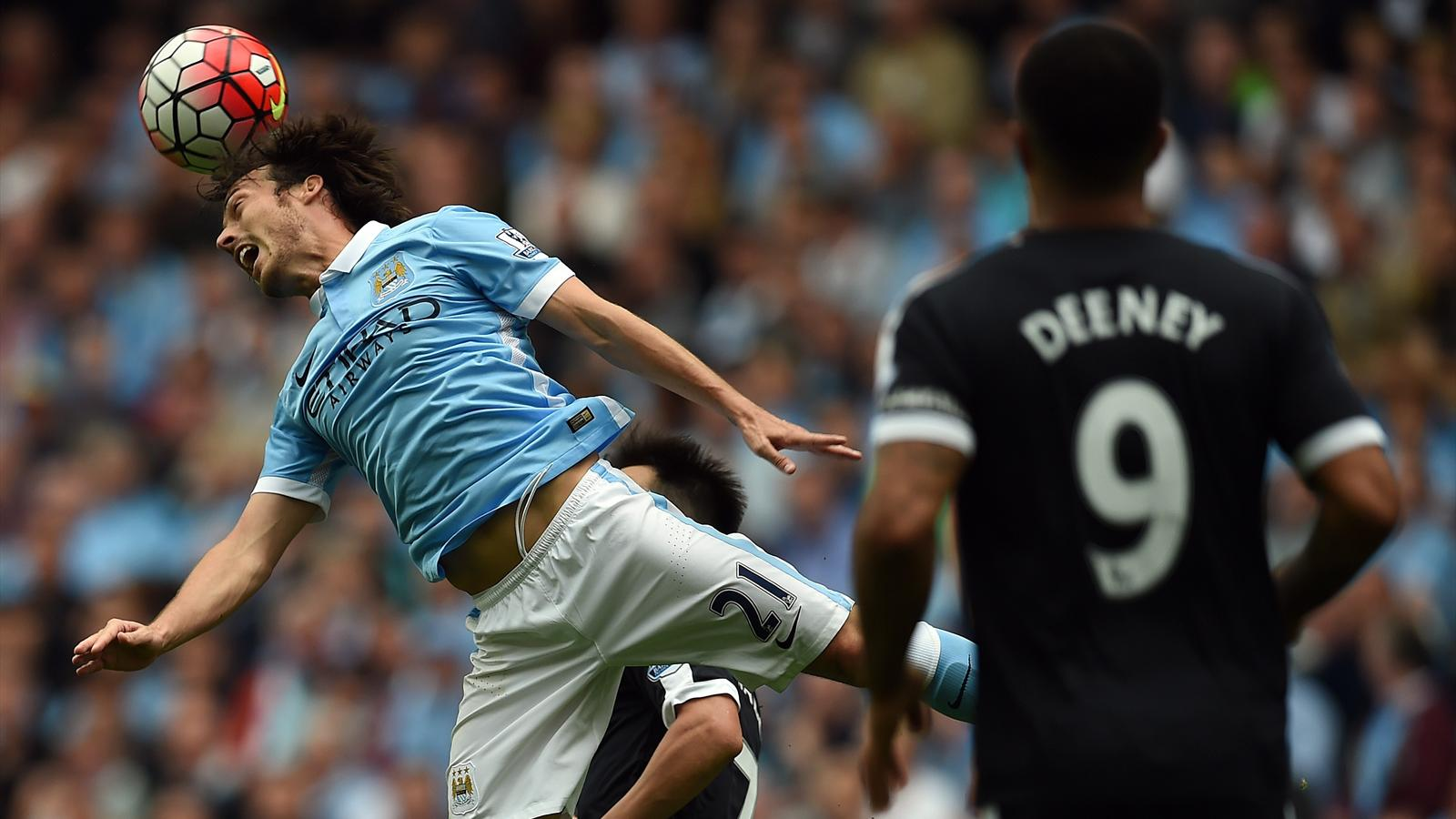 Manchester City's Spanish midfielder David Silva jumps for the ball