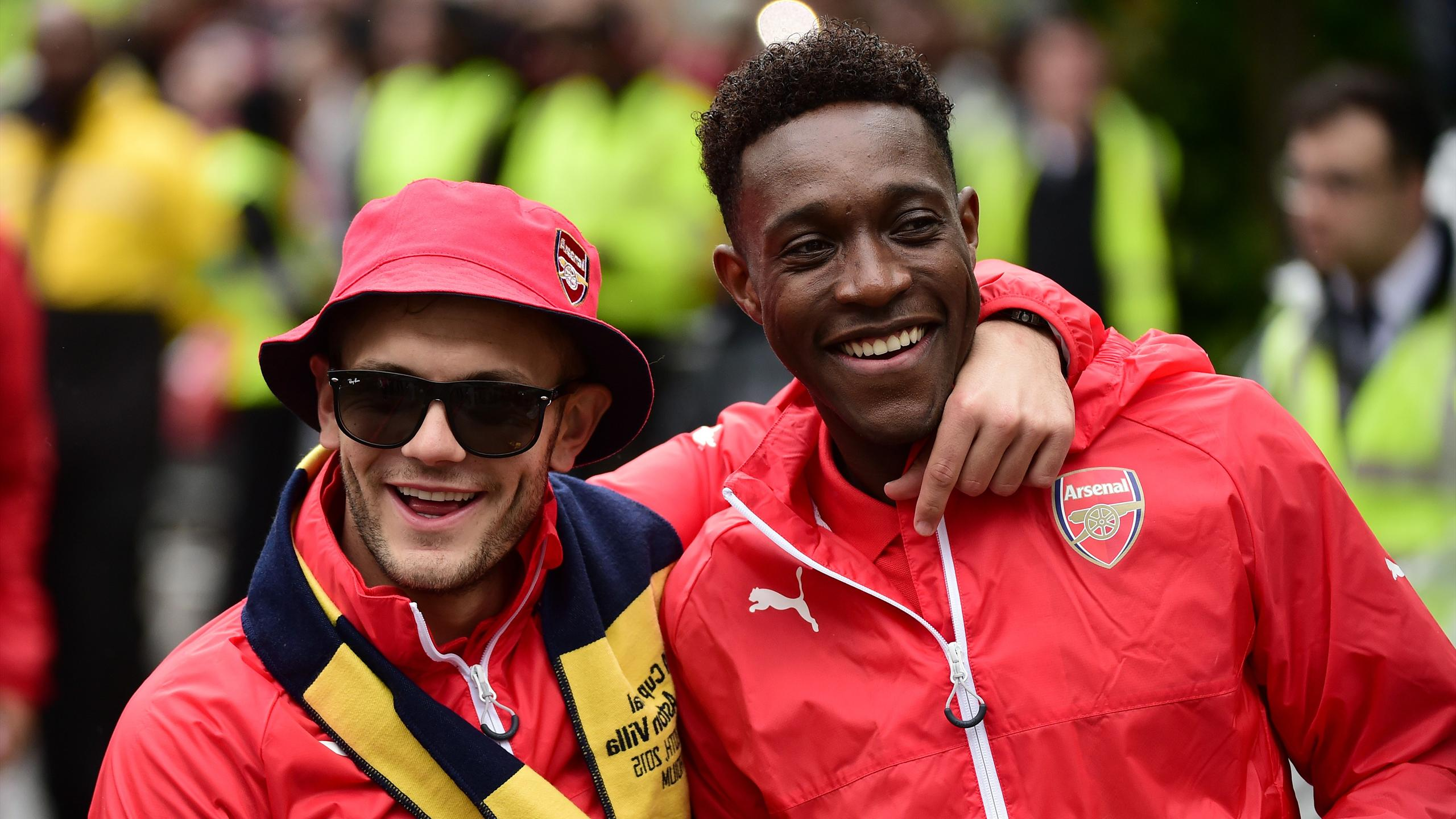 Arsenal's English midfielder Jack Wilshere and Arsenal's English striker Danny Welbeck react during the Arsenal victory parade in London on May 31, 2015