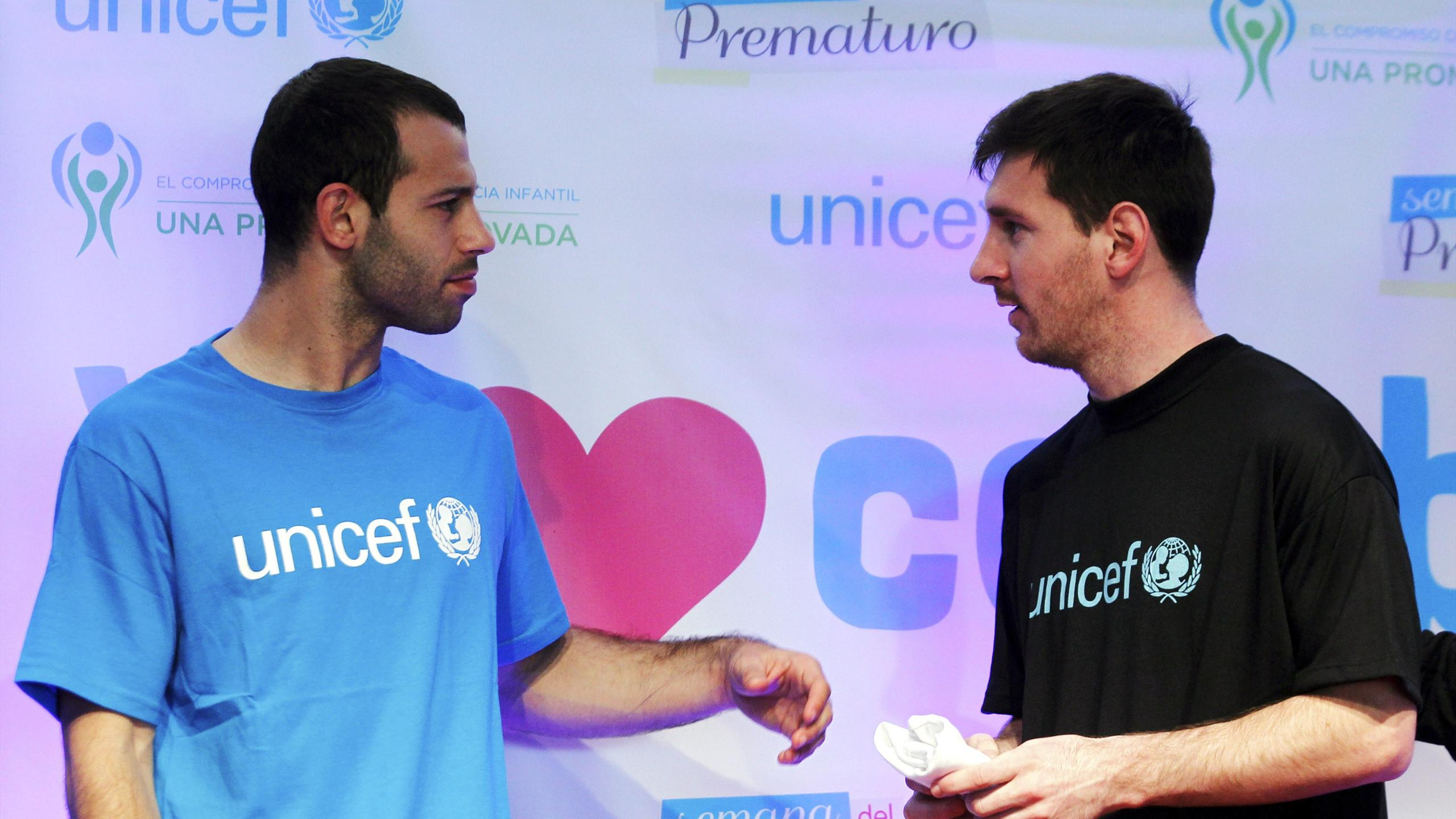 Argentina's Lionel Messi (R) and Javier Mascherano attend a UNICEF event at the squad's headquarters in Buenos Aires
