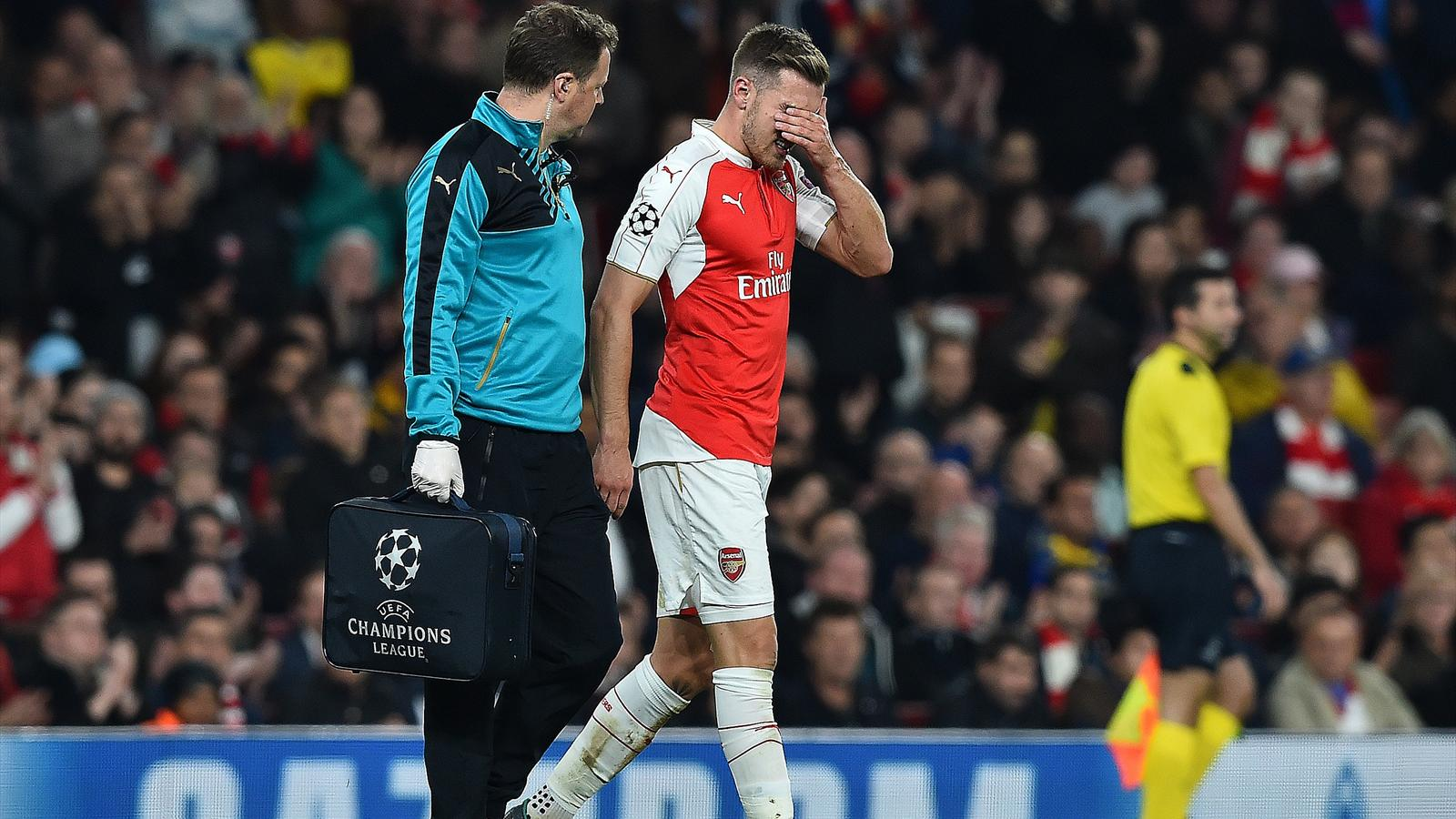 Arsenal's Welsh midfielder Aaron Ramsey (R) leaves the pitch injured during the UEFA Champions League football match between Arsenal and Bayern Munich