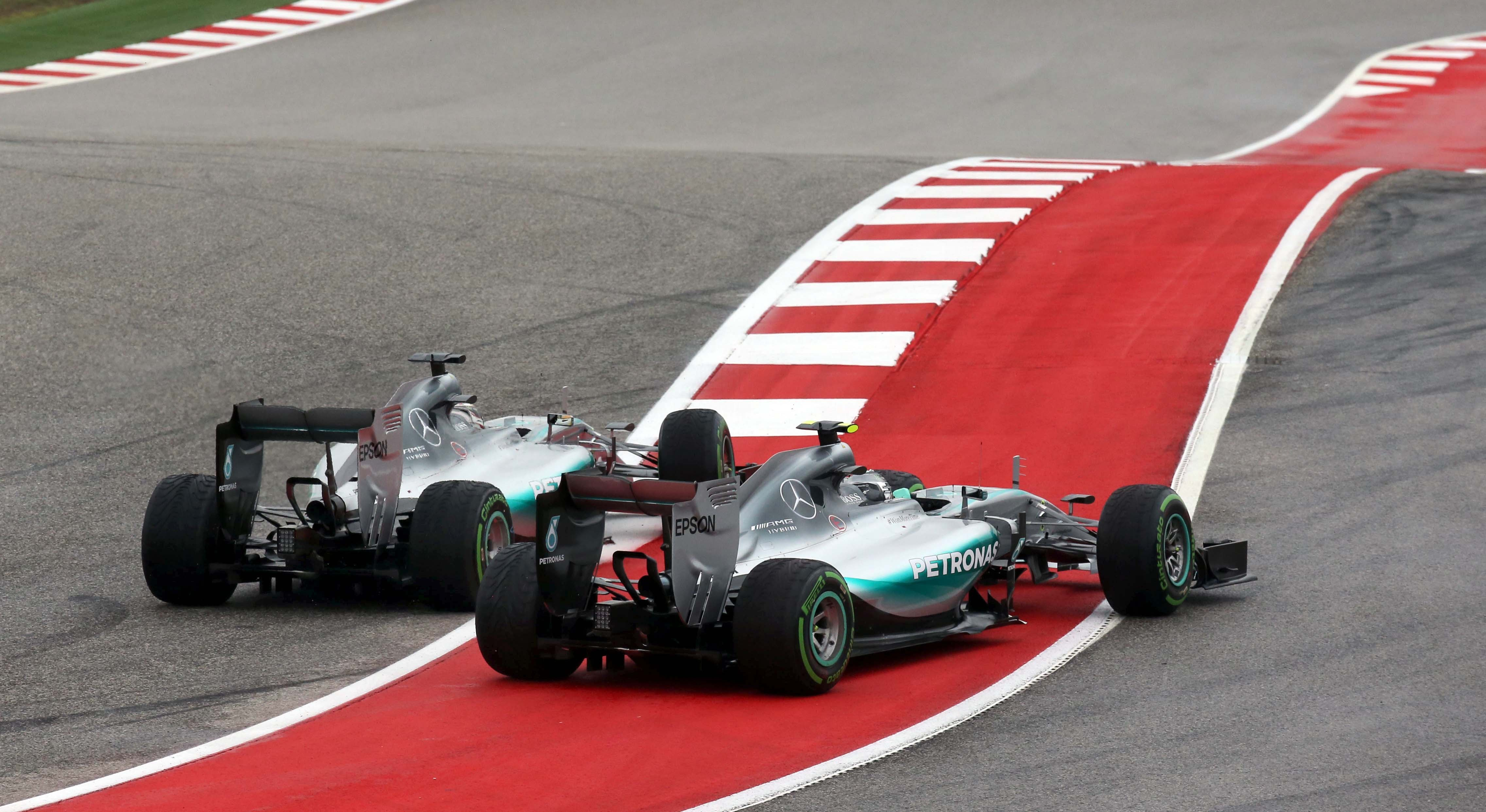Lewis Hamilton (left) pushes Nico Rosberg wide on the first corner