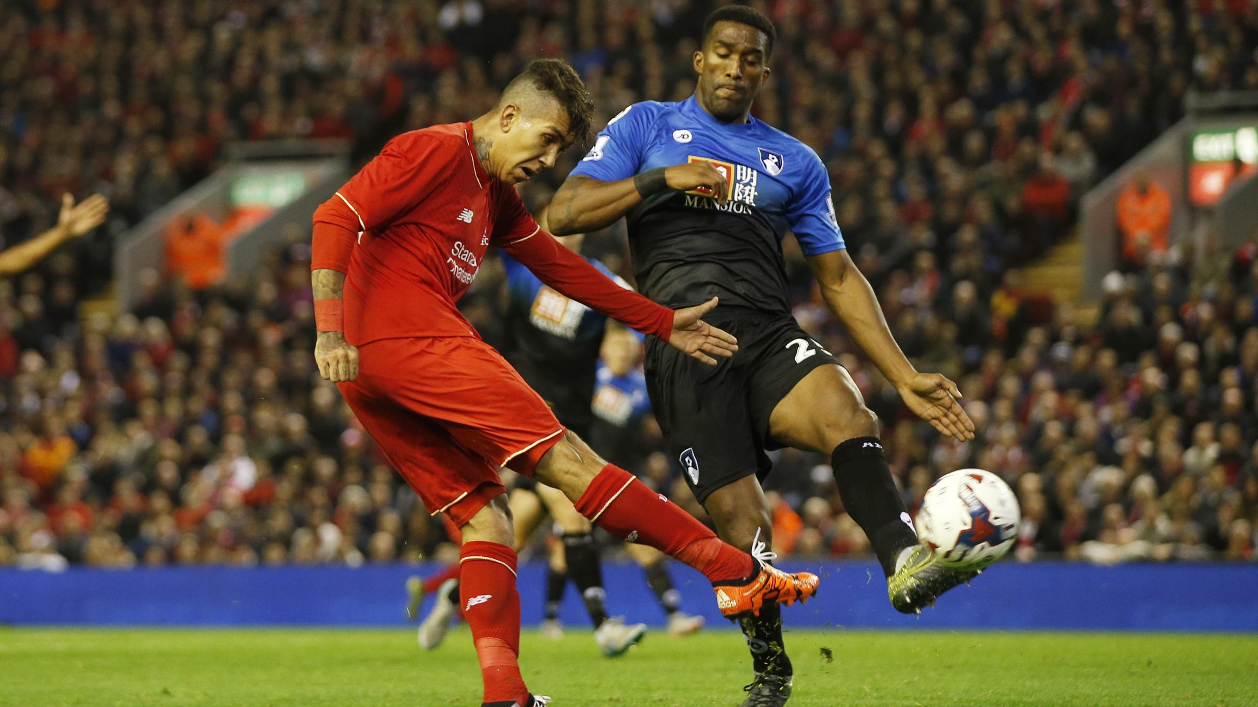 Liverpool's Roberto Firmino gets a shot off as Sylvain Distin challenges