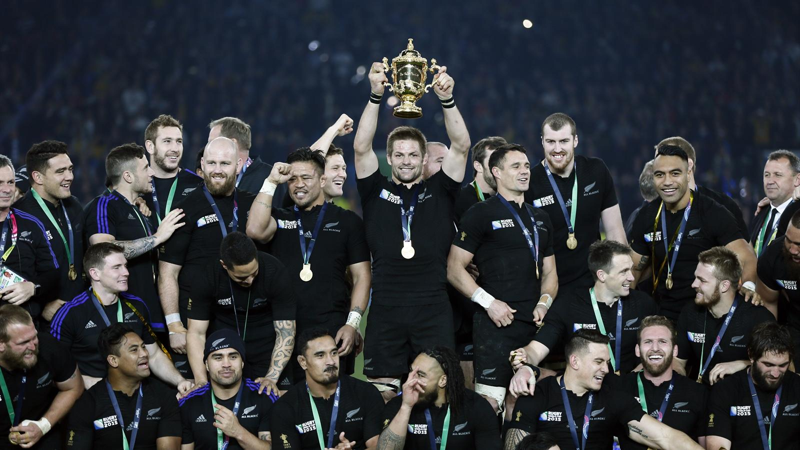 Richie McCaw of New Zealand (C) holds up the Webb Ellis trophy after winning the Rugby World Cup Final against Australia at Twickenham