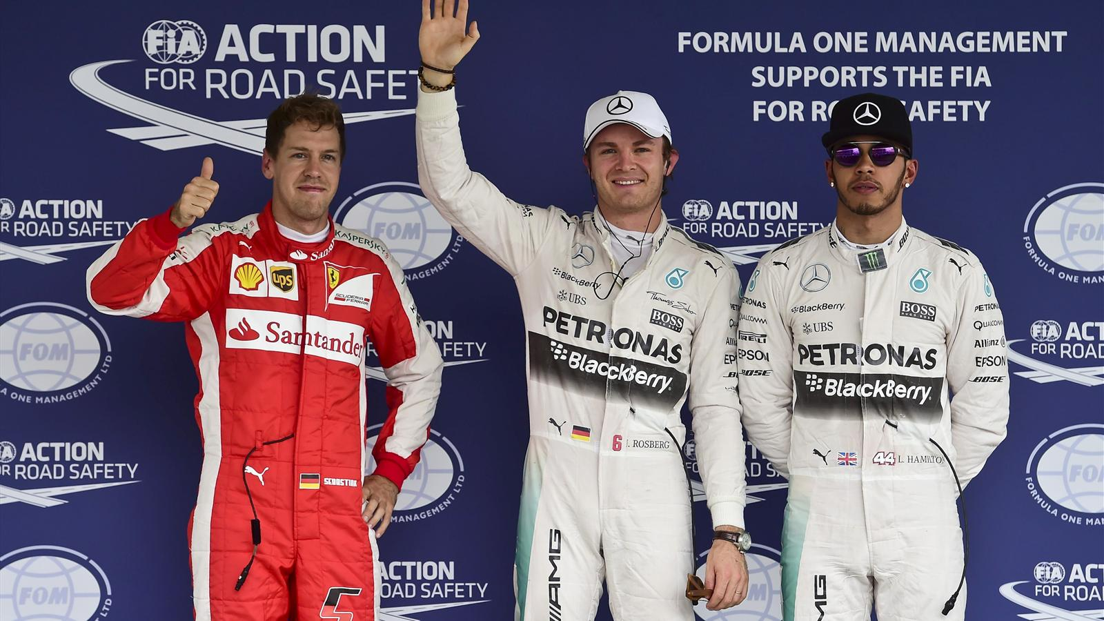 Mercedes Formula One drivers Lewis Hamilton of Britain (R) and Nico Rosberg of Germany pose with Ferrari Formula One driver Sebastian Vettel of Germany (L) after the qualifying session for the Mexican F1 Grand Prix