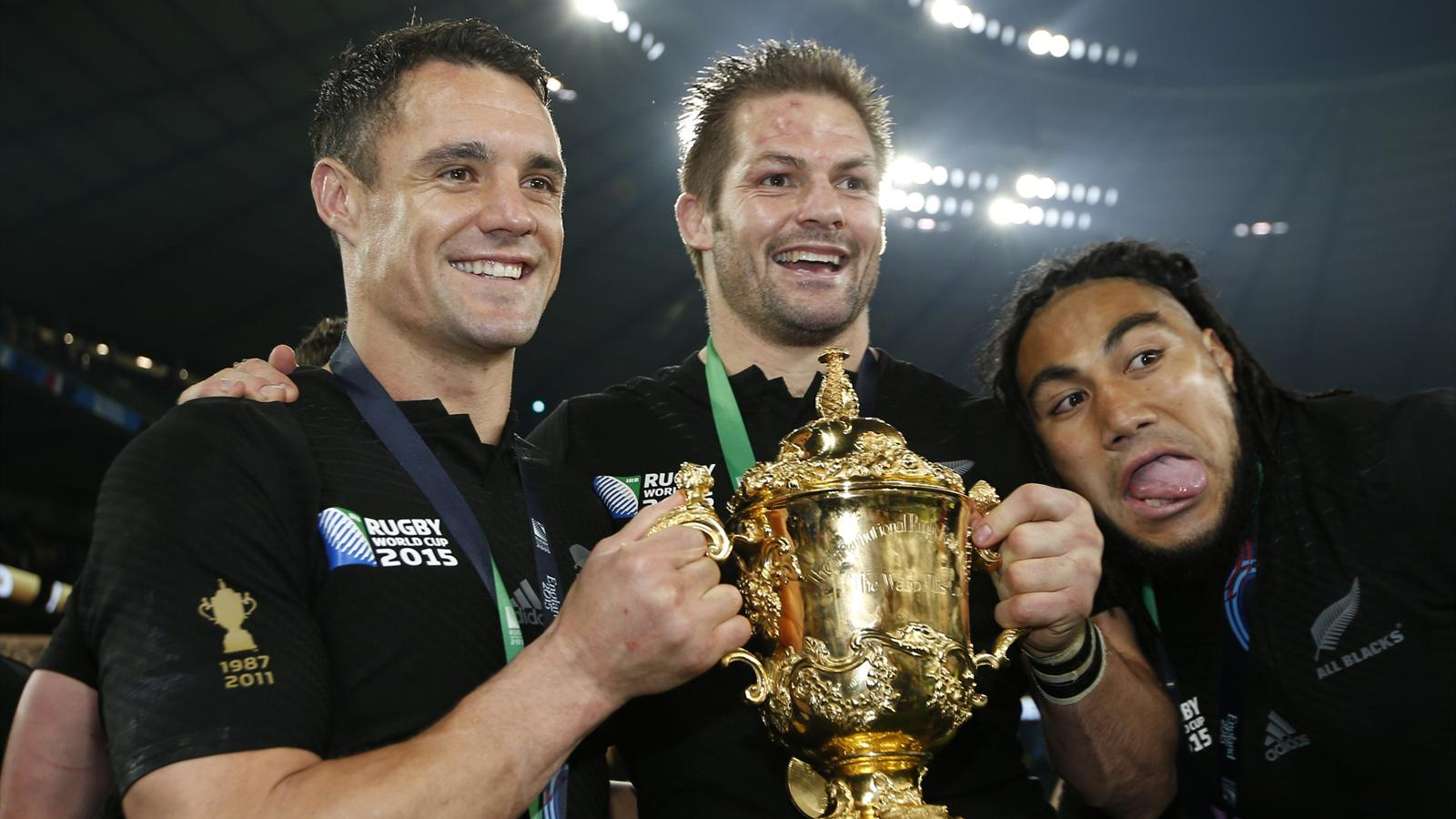 Richie McCaw of New Zealand (C) holds the Webb Ellis Cup as he celebrates with teammates Dan Carter (L) and Ma'a Nonu (R) after beating Australia to win the Rugby World Cup final match at Twickenham