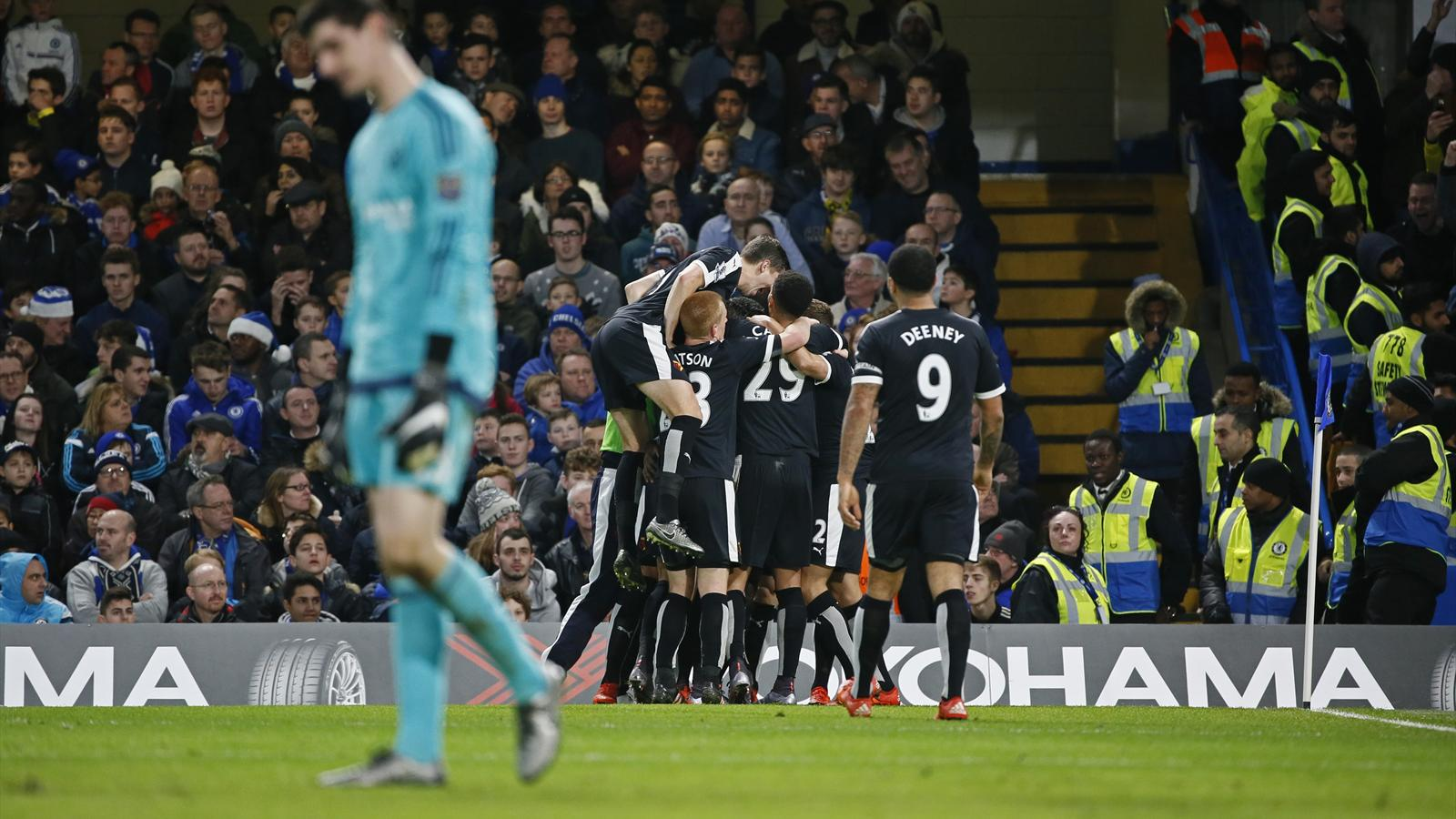 Odion Ighalo celebrates with team mates after scoring the second goal for Watford as Chelsea's Thibaut Courtois looks dejected