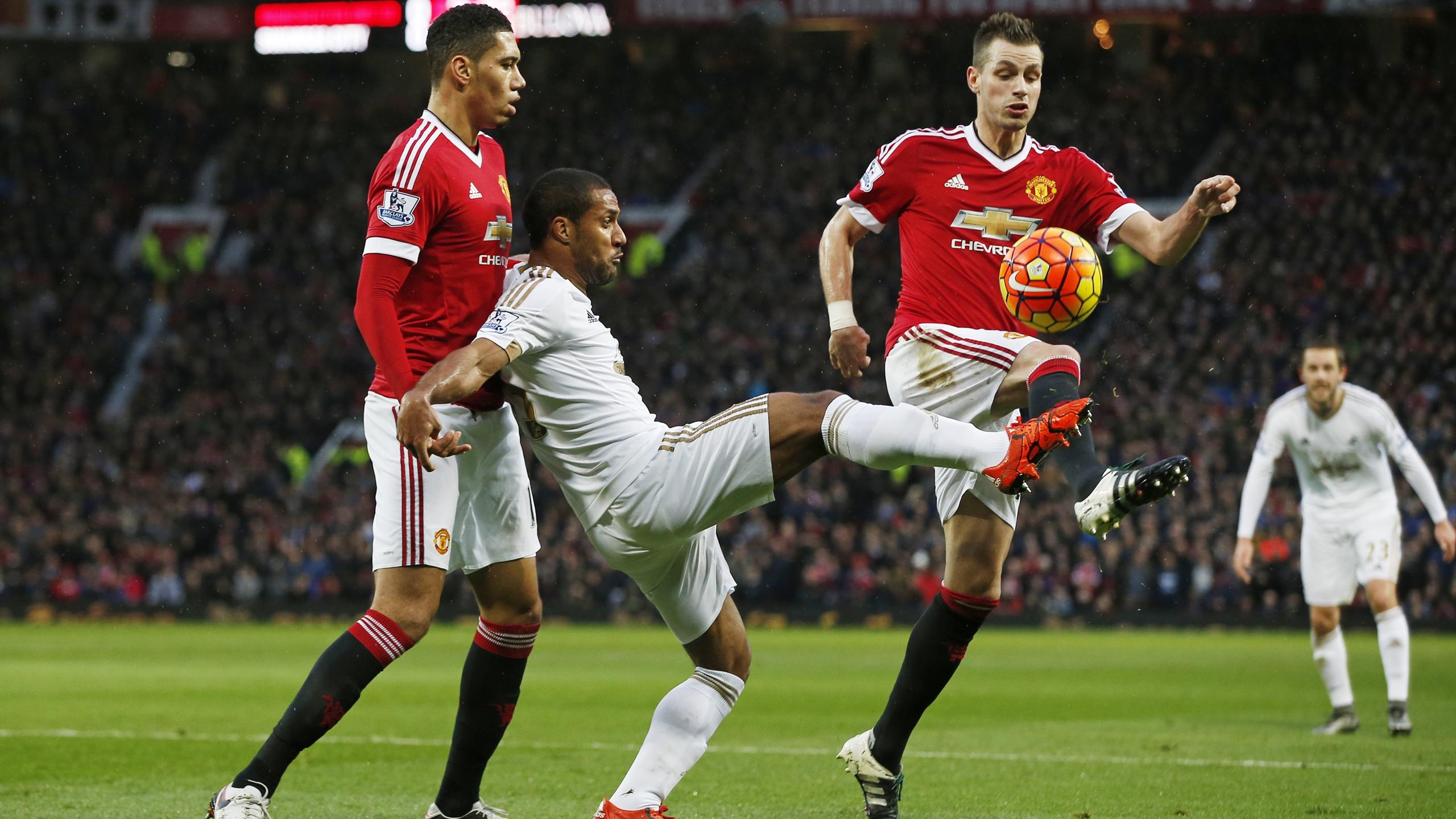 Swansea's Wayne Routledge under pressure against Manchester United