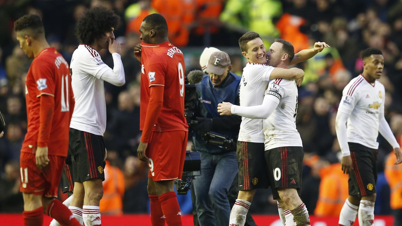 Liverpool's Christian Benteke and Manchester United's Marouane Fellaini as Ander Herrara and Wayne Rooney celebrate at the end of the match