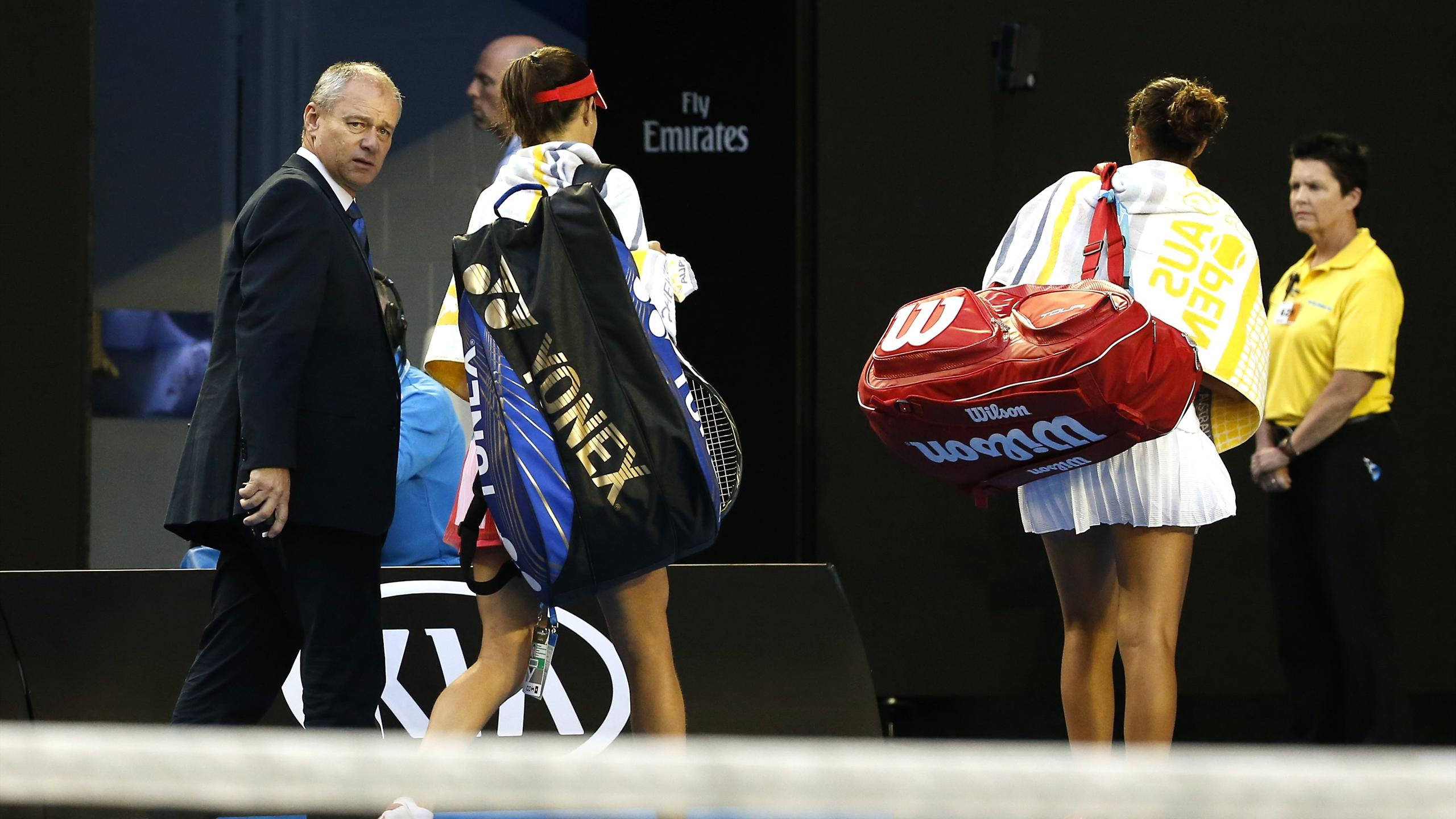 Serbia's Ana Ivanovic (C) and Madison Keys of the U.S. leave with their bags as play in their third round match is suspended due to a spectator requiring medical attention, at the Australian Open