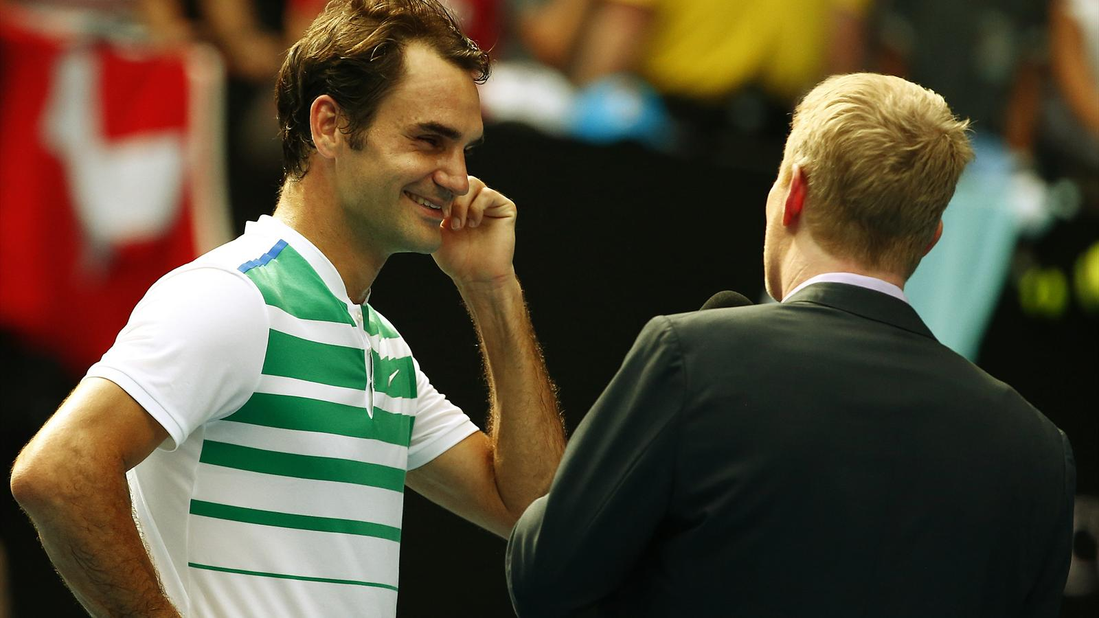Switzerland's Roger Federer smiles as he talks to former tennis player Jim Courier during an interview after winning his quarter-final match against Czech Republic's Tomas Berdych at the Australian Open