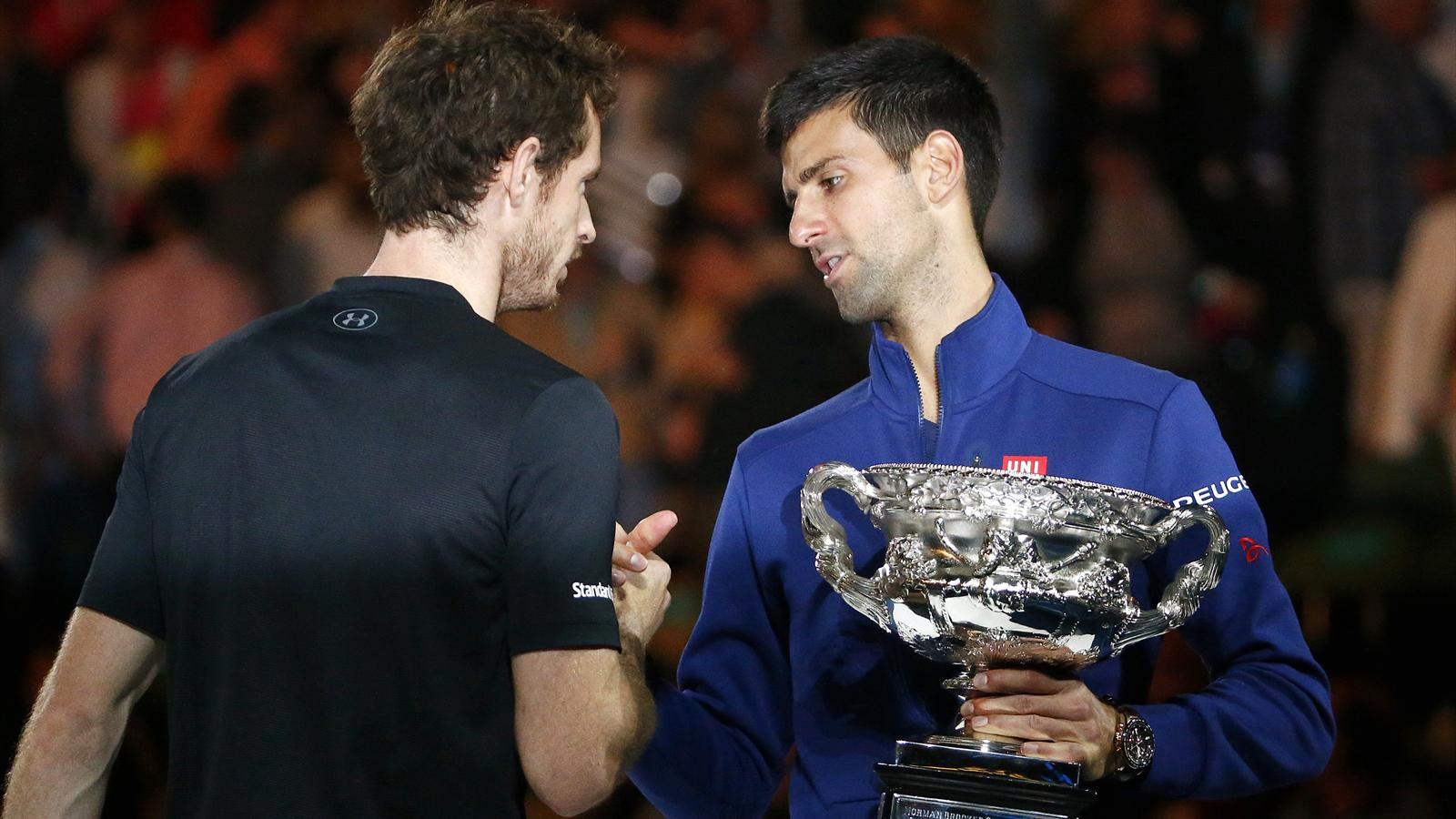 Serbia's Novak Djokovic (R) shakes hands with Britain's Andy Murray while holding the men's singles trophy after winning their final match at the Australian Open