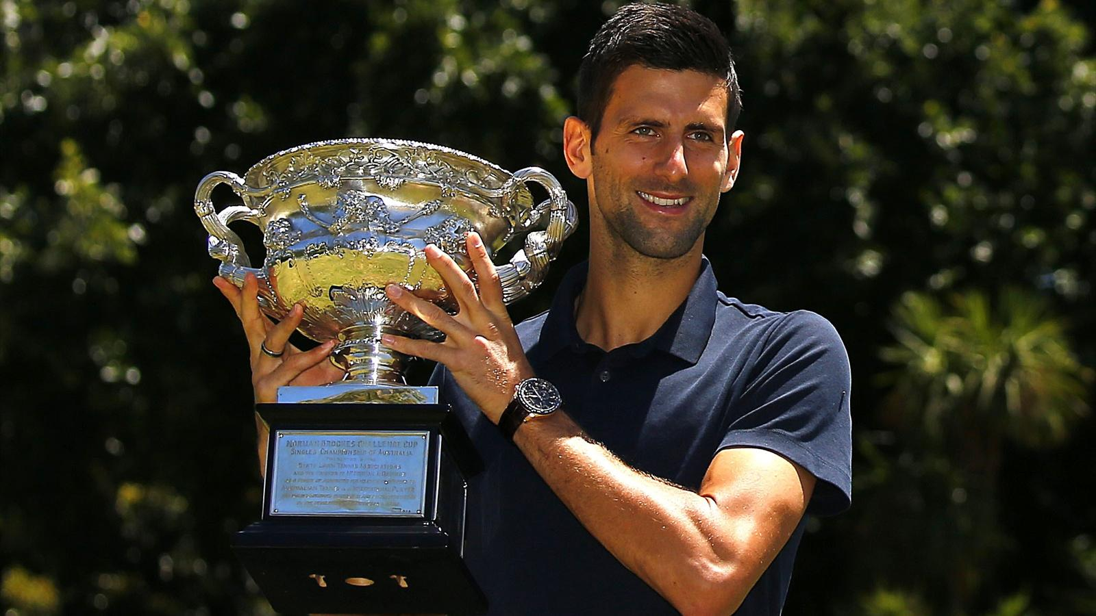 Serbia's Novak Djokovic poses with the men's singles trophy, a day after winning his final match at the Australian Open at Government Hill in Melbourne