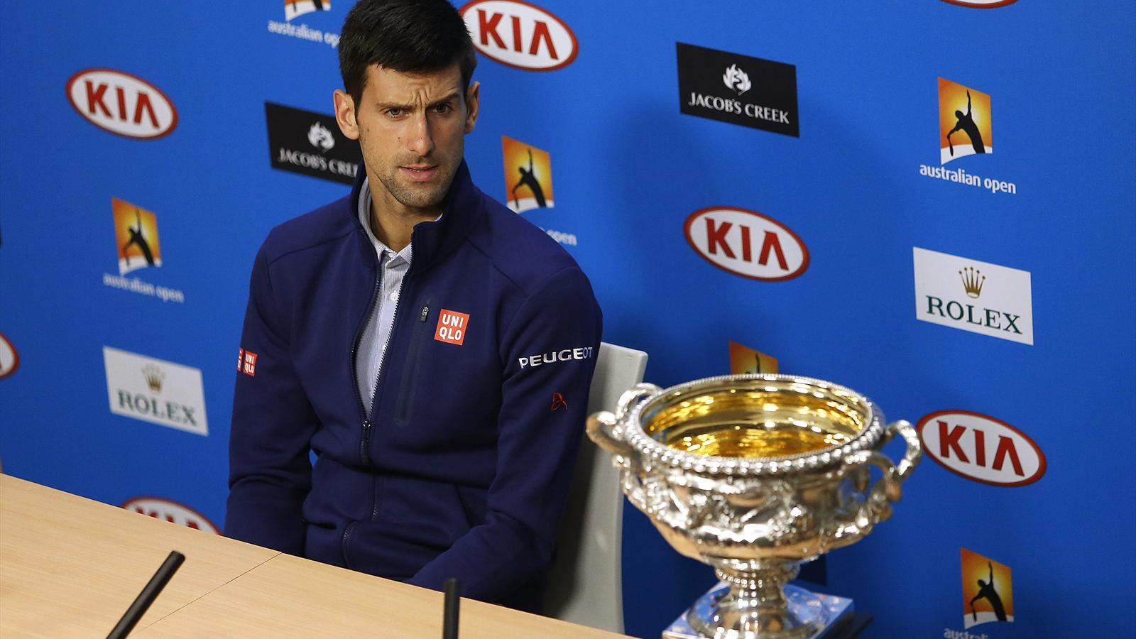 Serbia's Novak Djokovic sits beside the men's singles trophy during a news conference after winning the men's singles final match at the Australian Open