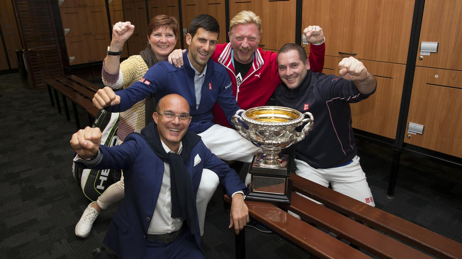Serbia's Novak Djokovic celebrates with his coach Boris Becker and members of the training staff in the locker room after winning his final match against Britain's Andy Murray at the Australian Open