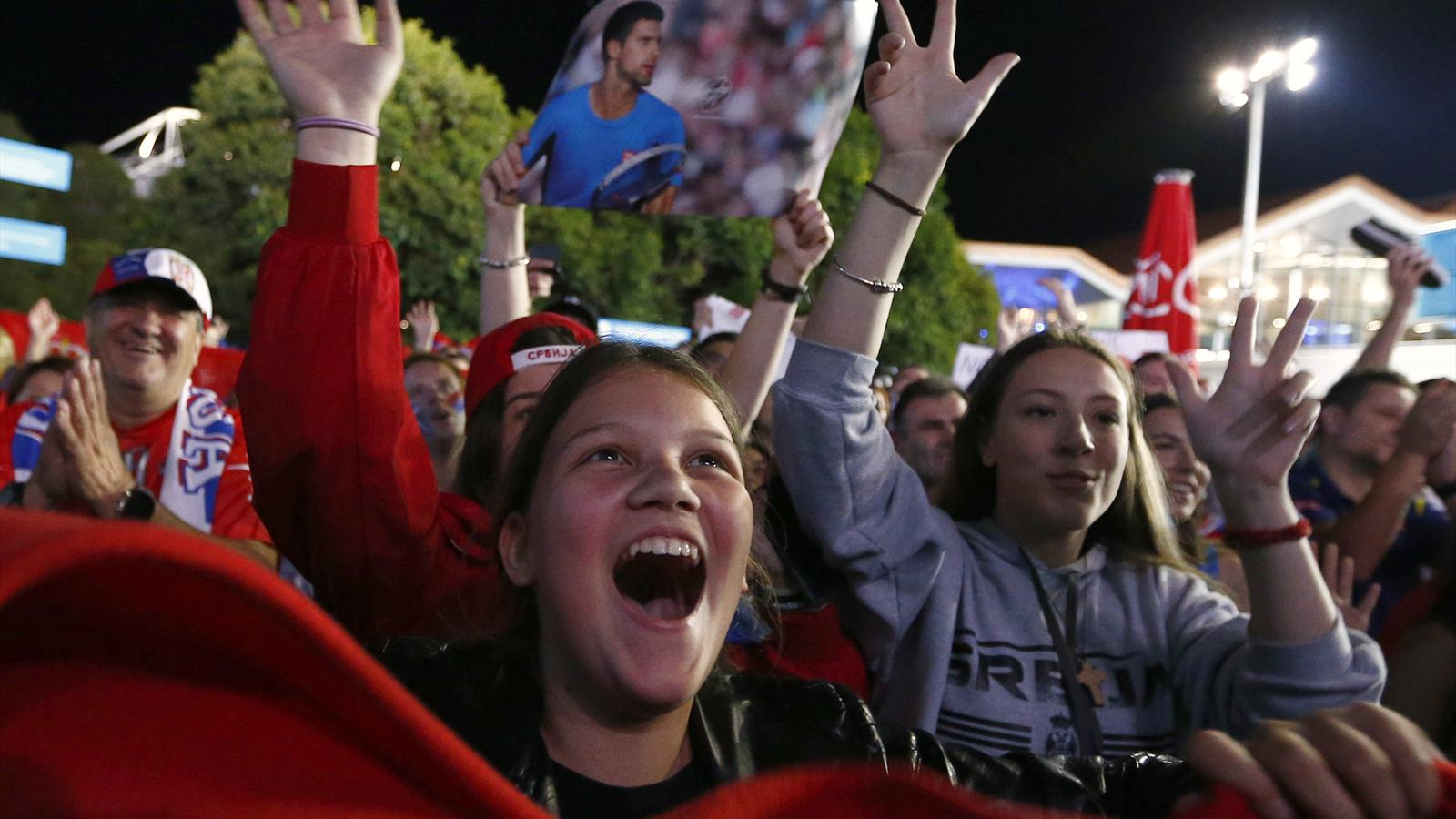 Supporters of Serbia's Novak Djokovic celebrate as they wait for him to appear after he won his final match against Britain's Andy Murray at the Australian Open