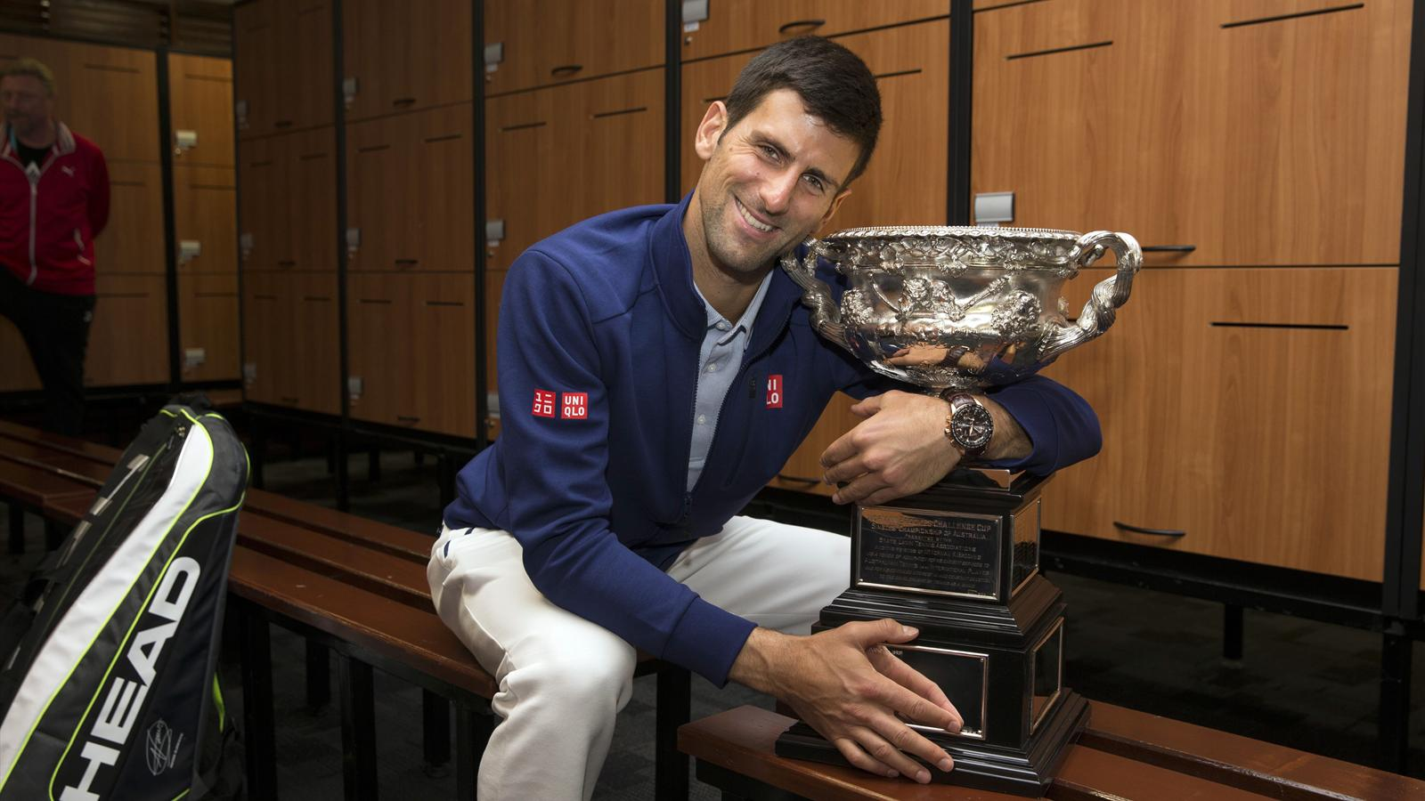 Serbia's Novak Djokovic poses with the men's singles trophy in the locker room after winning his final match against Britain's Andy Murray at the Australian Open