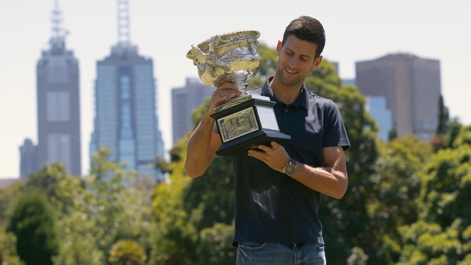 Serbia's Novak Djokovic looks at the men's singles trophy during a photocall, a day after winning his final match at the Australian Open