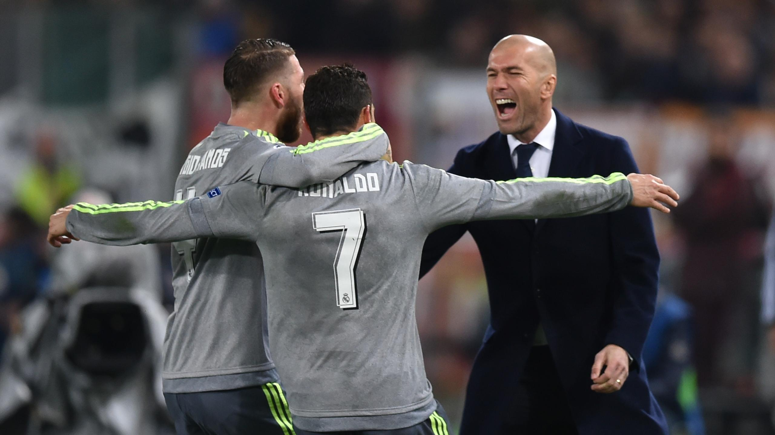 Real Madrid's Portuguese forward Cristiano Ronaldo (C) celebrates with Real Madrid's defender Sergio Ramos and Real Madrid's French coach Zinedine Zidane after scoring during the UEFA Champions League football match AS Roma vs Real Madrid on Frebruary 17,