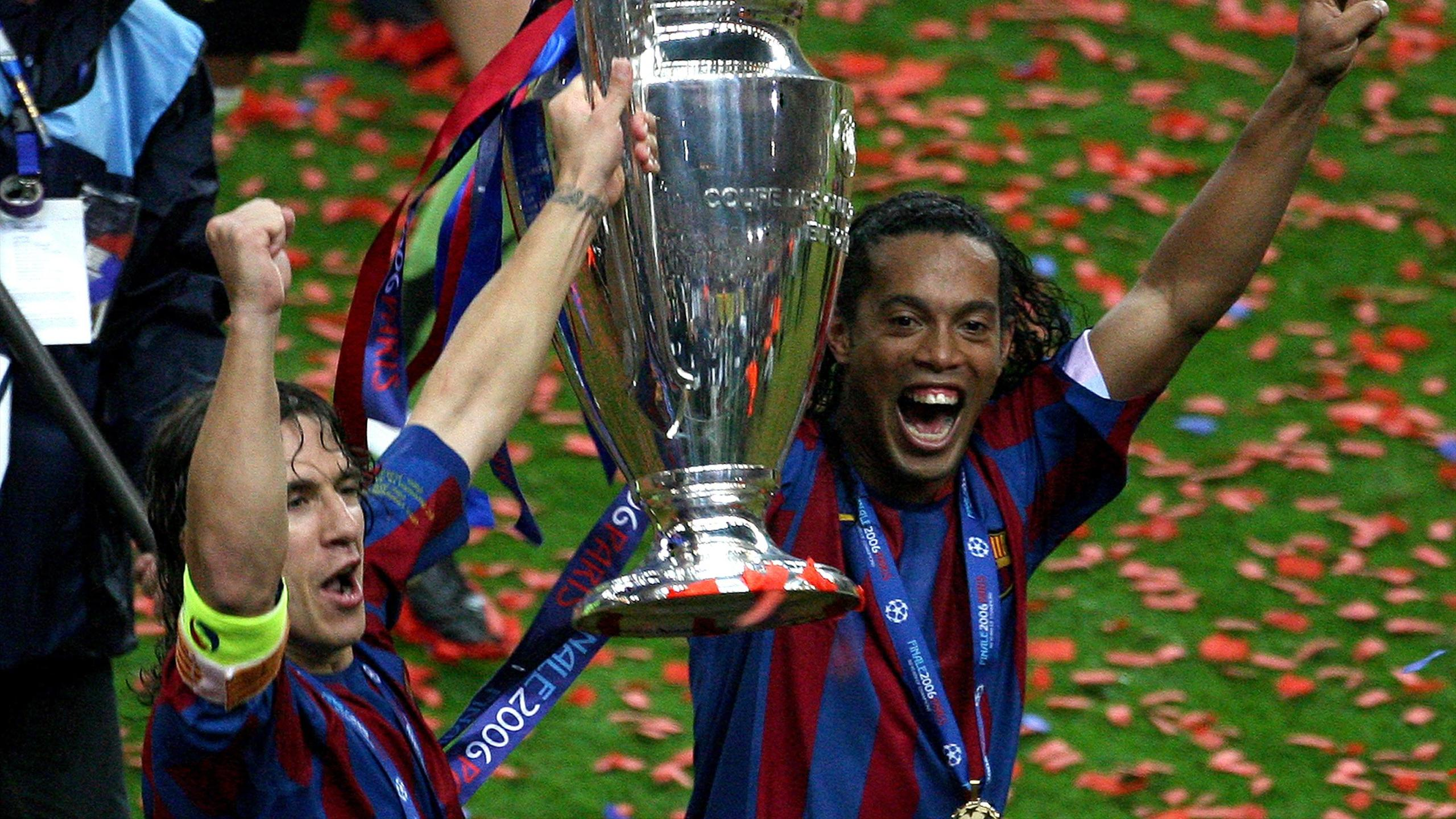 Barcelona's Ronaldinho of Brazil (R) celebrates with Carles Puyol after winning the Champions League final against Arsenal at the Stade de France