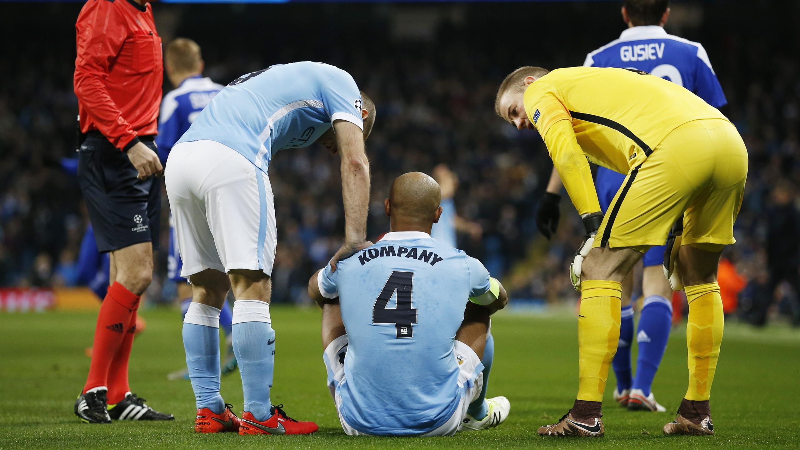 Manchester City's Vincent Kompany looks dejected after sustaining an injury as Joe Hart and Pablo Zabaleta look on