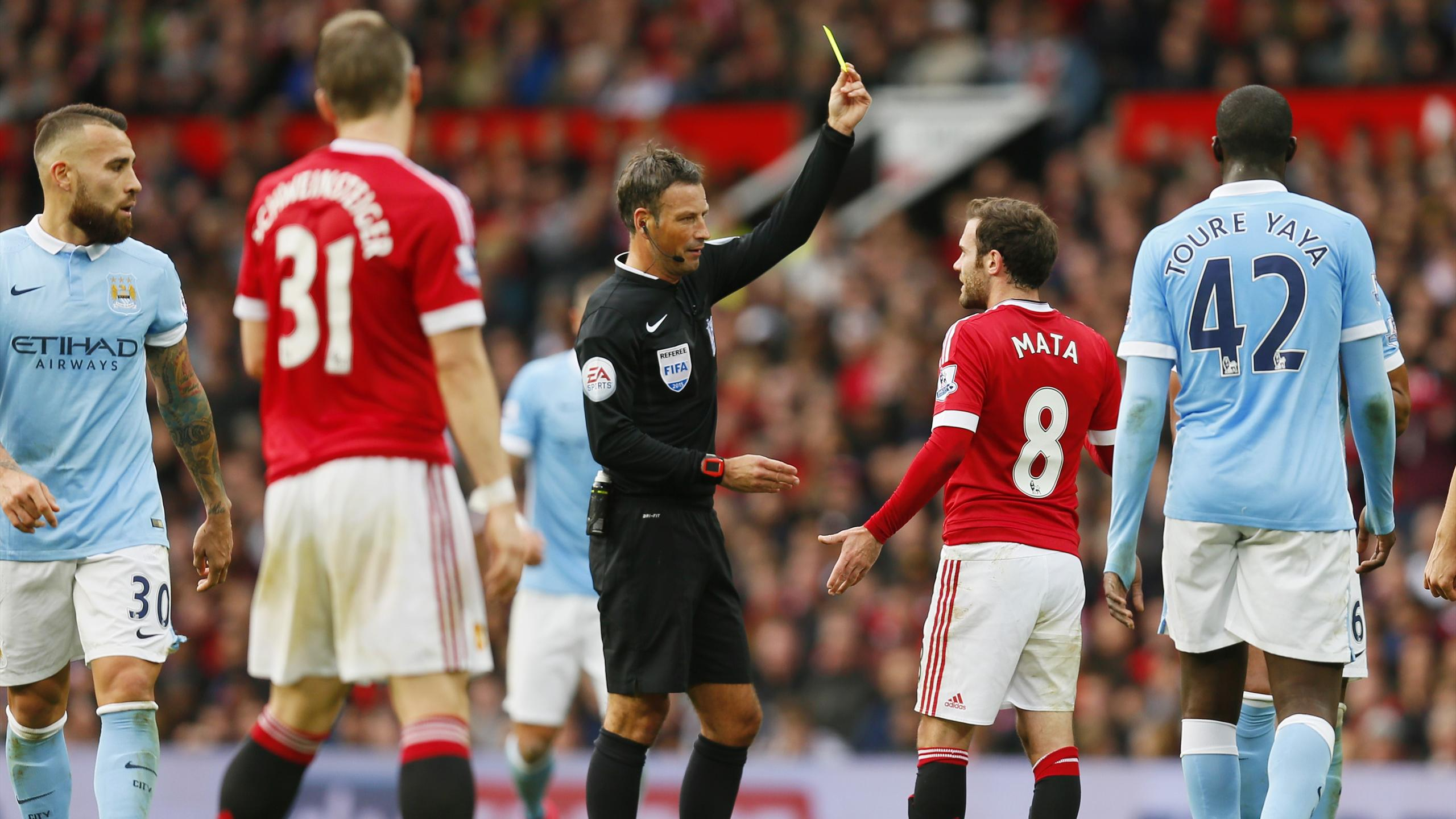 Manchester United's Juan Mata is booked by referee Mark Clattenburg
