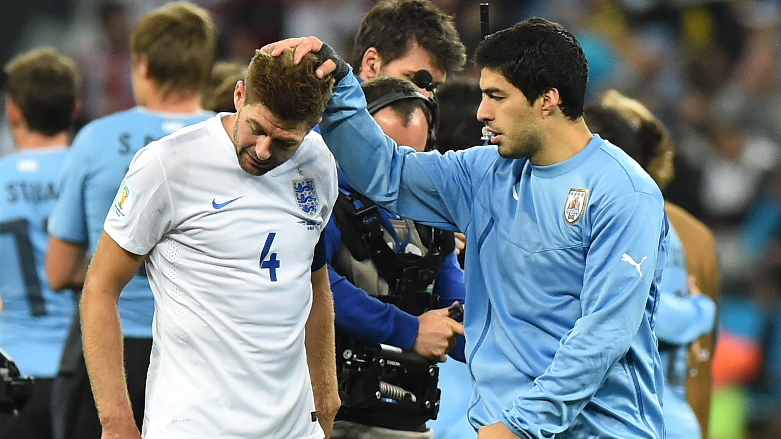 England's midfielder and captain Steven Gerrard (L) is consoled by Uruguay's forward Luis Suarez