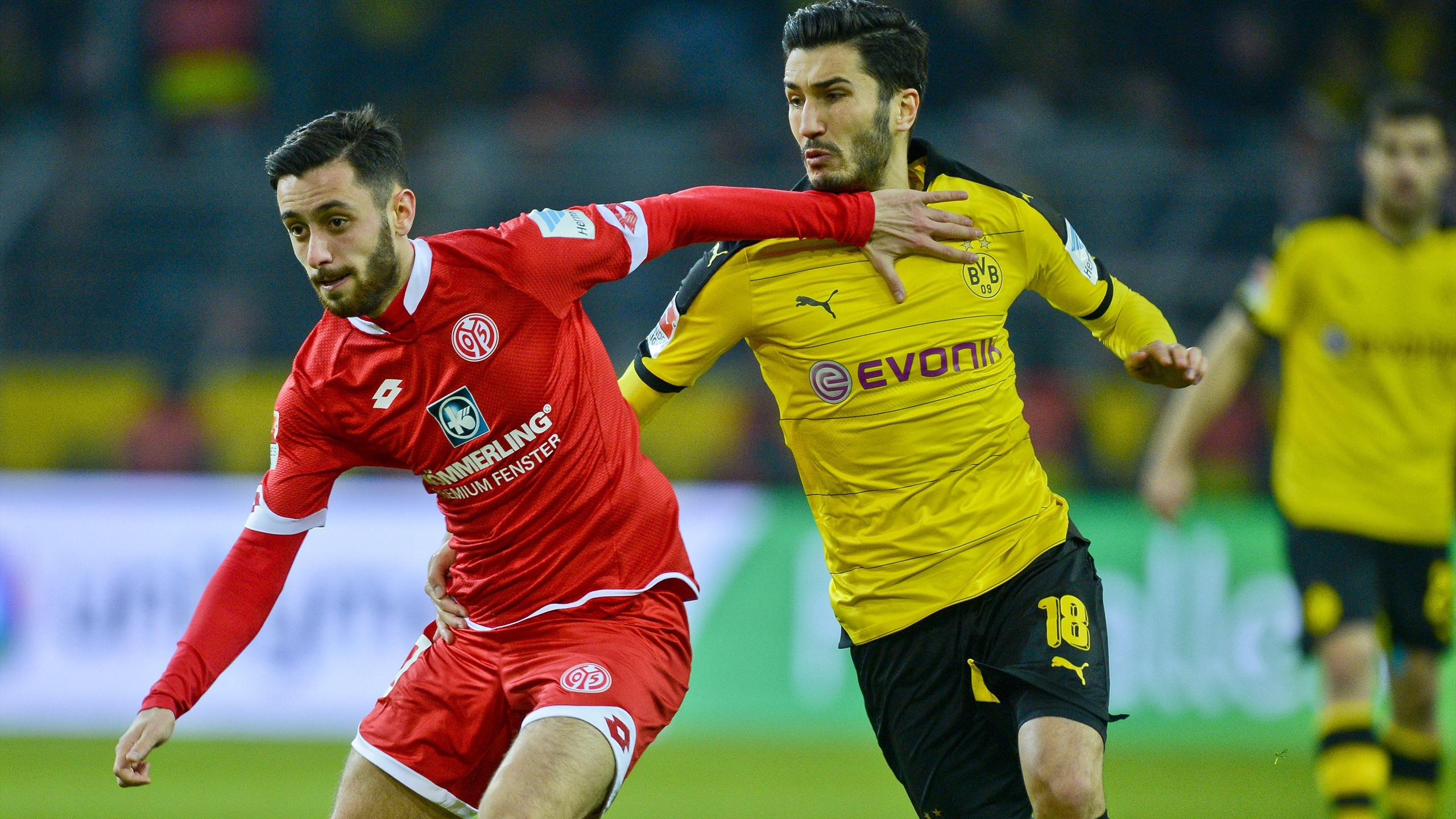 Dortmund's Nuri Sahin (R) and Mainz's Yunus Malli vie for the ball during the German first division Bundesliga football match Borussia Dortmund v 1 FSV Mainz 05 in Dortmund, on March 13, 2016.