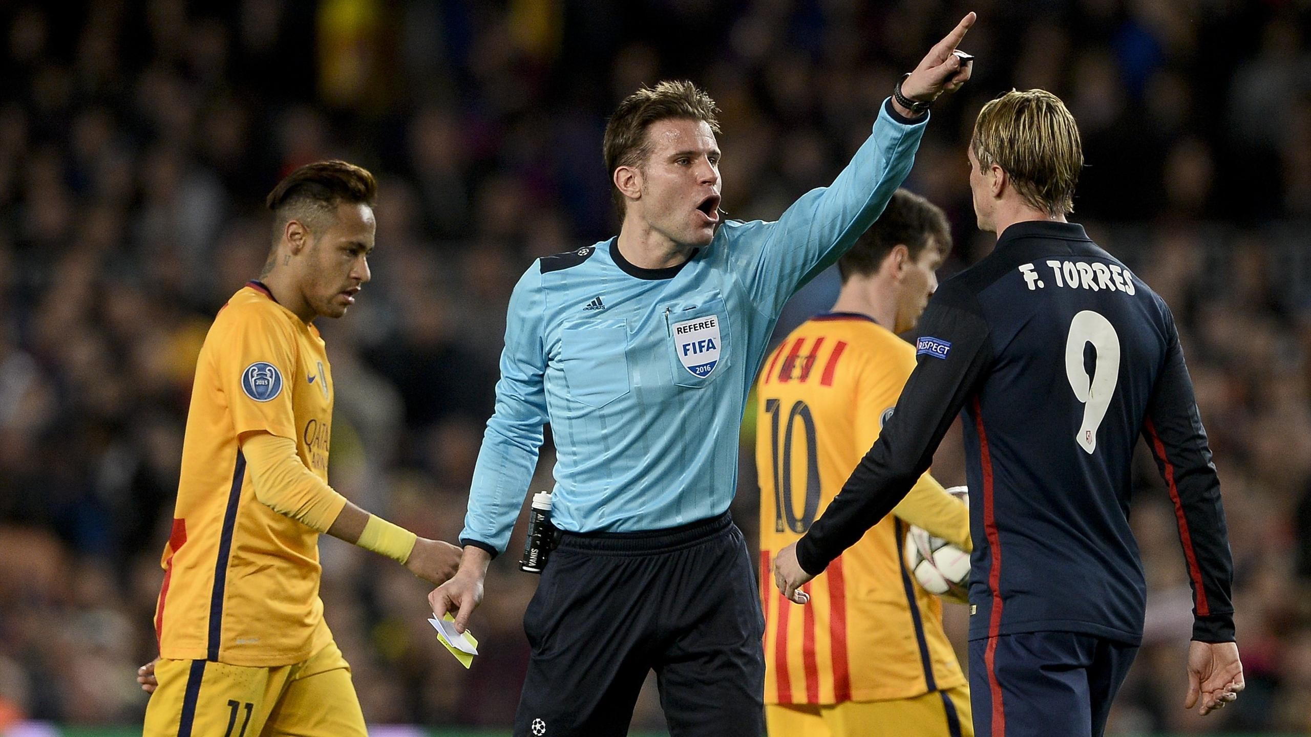 Felix Brych (C) gestures after showing a yellow card to Atletico Madrid's forward Fernando Torres (R)