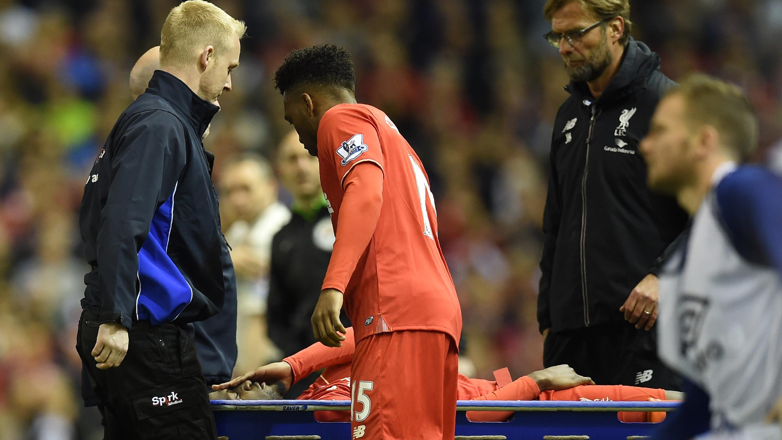Liverpool's English striker Daniel Sturridge (C) and Liverpool's German manager Jurgen Klopp (R) look at Liverpool's Belgian striker Divock Origi as he is stretchered off during the English Premier League football match between Liverpool and Everton