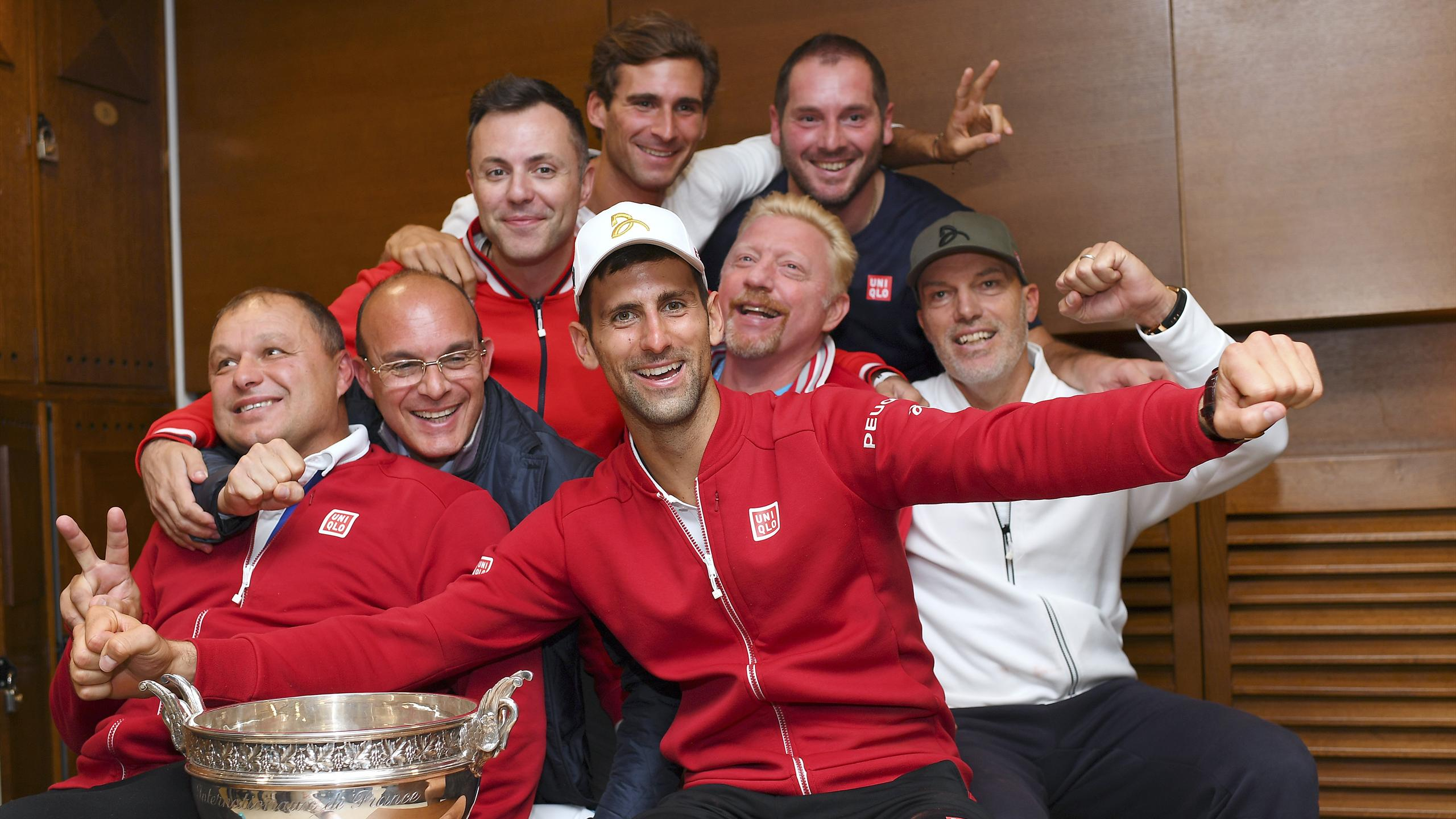 erbia's Novak Djokovic (C) posing with his trophy flanked by his coach former German tennis player Boris Becker (C-R) in the locker room after winning the men's final match against Britain's Andy Murray at the Roland Garros 2016 French Tennis Open in Pari