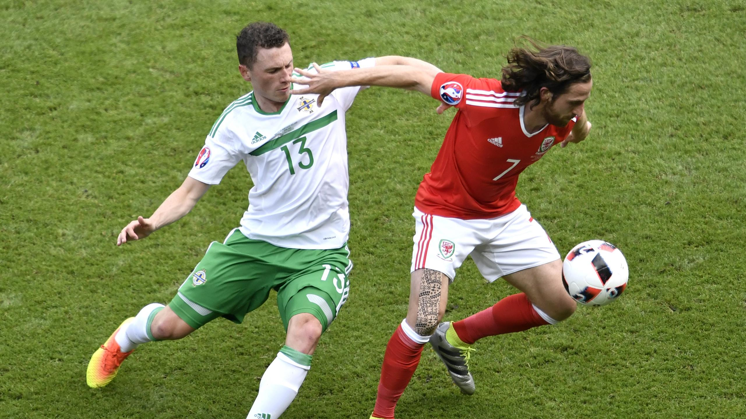 Northern Ireland's midfielder Corry Evans (L) challenges Wales' midfielder Joe Allen