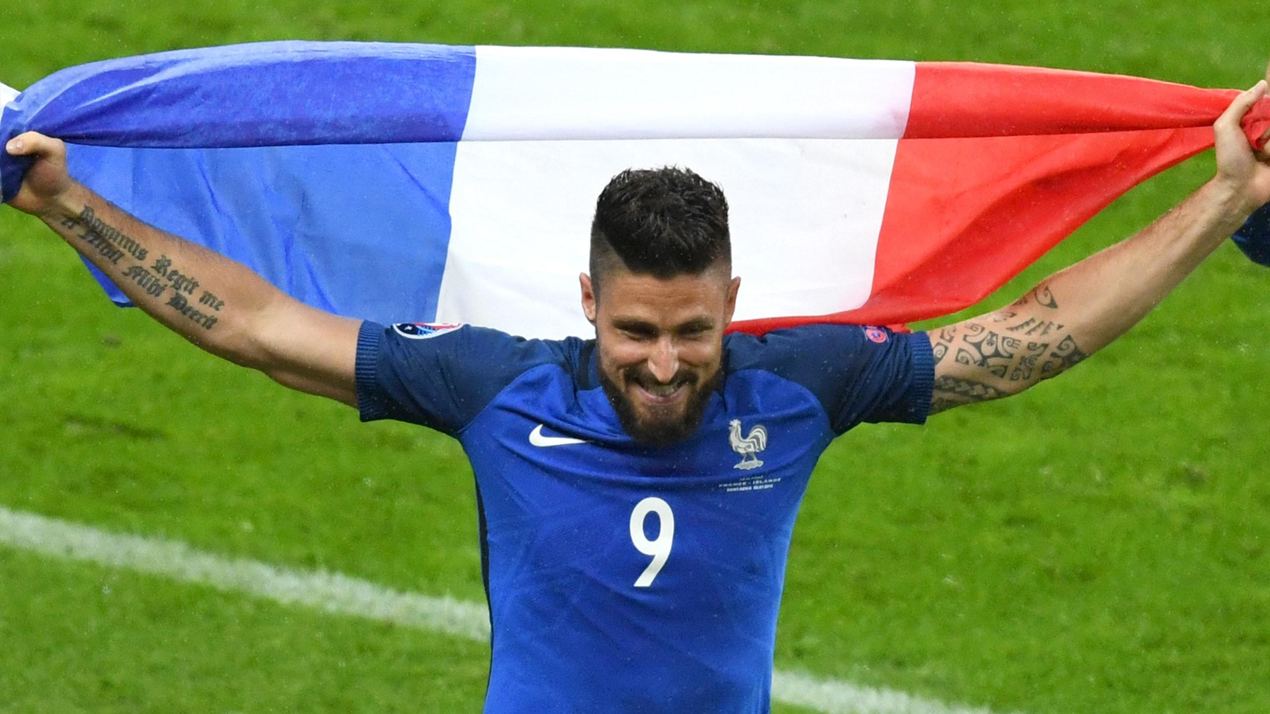 France's forward Olivier Giroud holds a French flag after winning the Euro 2016 quarter-final football match between France and Iceland