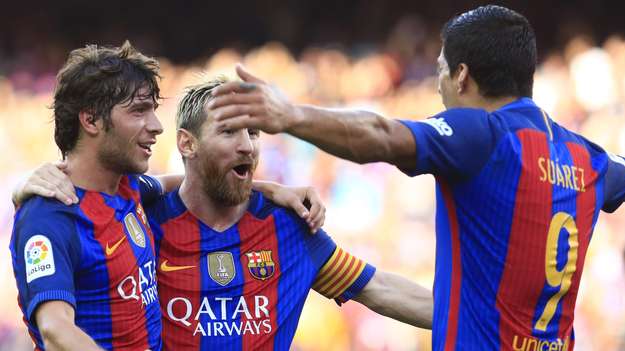 Barcelona's Argentinian forward Lionel Messi (C) celebrates after scoring with Barcelona's midfielder Sergi Roberto (L) and Barcelona's Uruguayan forward Luis Suarez